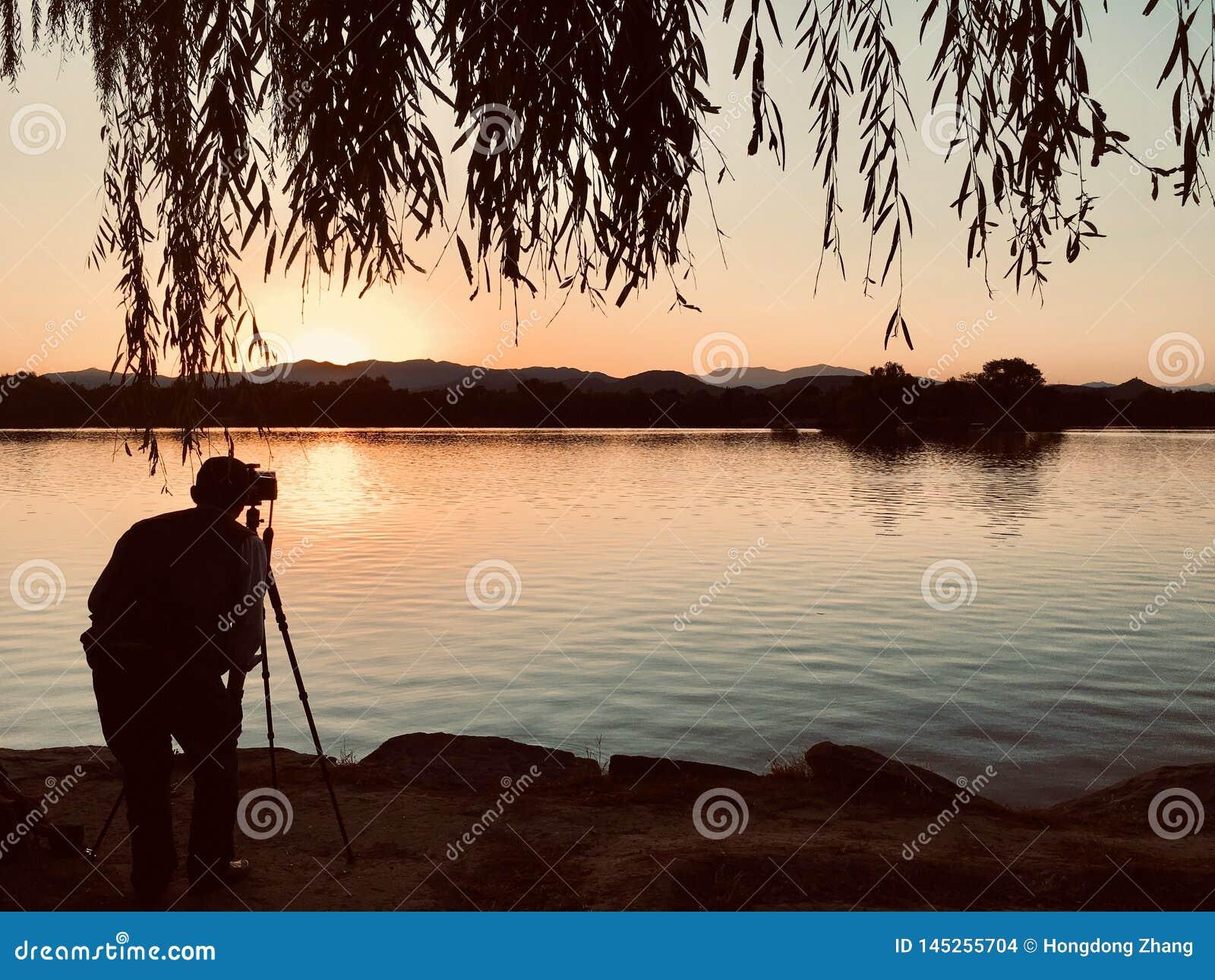 Tillbaka sikt av mannen som fotograferar solnedgång