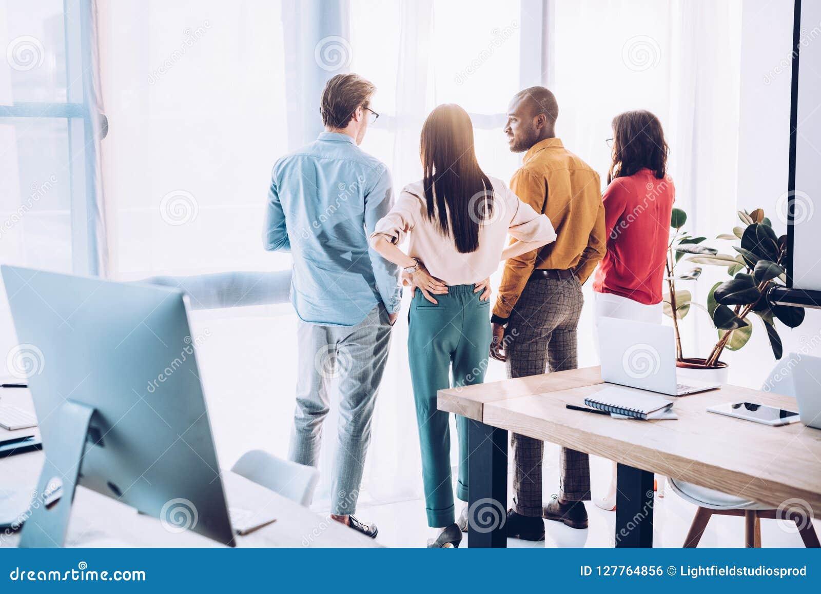 Tillbaka sikt av multietniska affärskollegor som ut ser fönstret