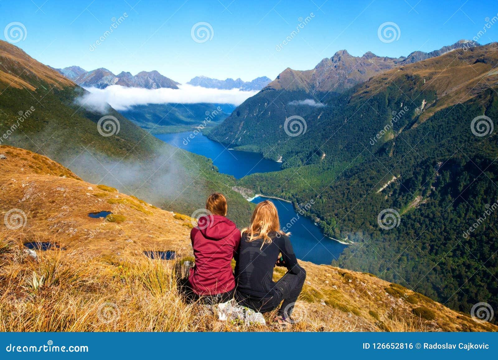 Tillbaka sikt av parhandelsresande framme av att bedöva sikten för bergdalsjö, nyckel- spår för toppmöteruttbrännskada, Fiordland