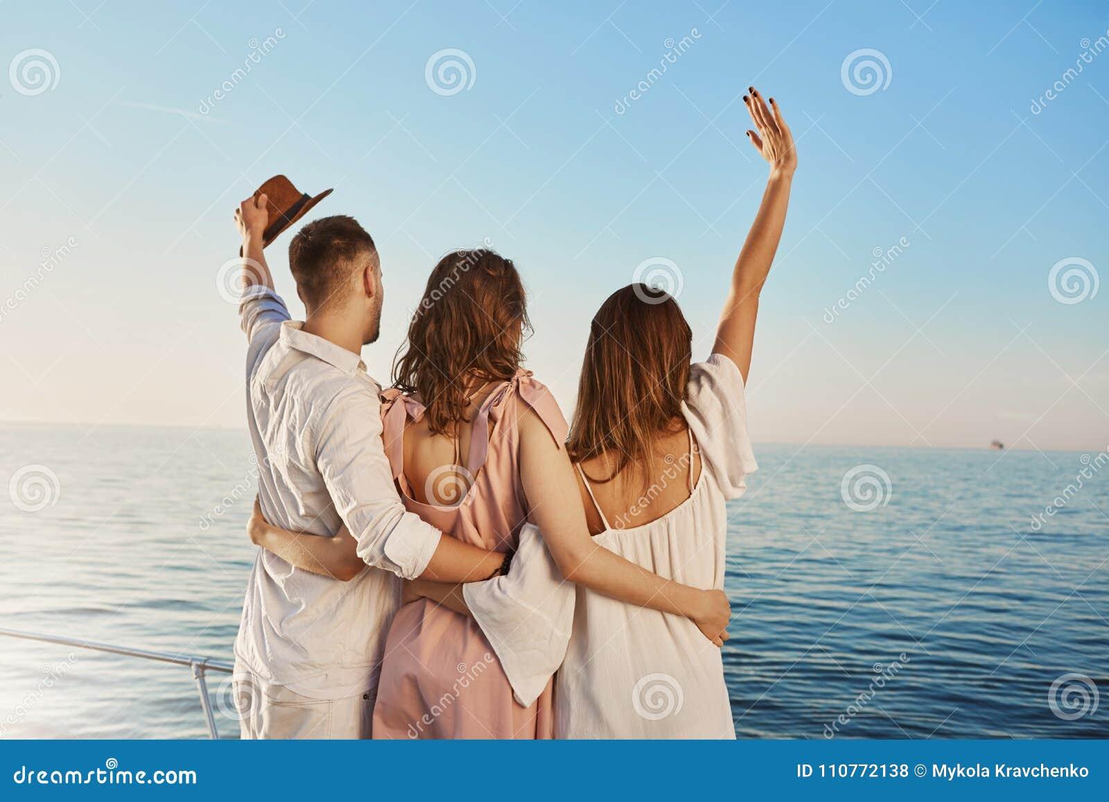 Tillbaka sikt av tre bästa vän som reser av fartyget som kramar och vinkar, medan se havet Folk som är på lyx