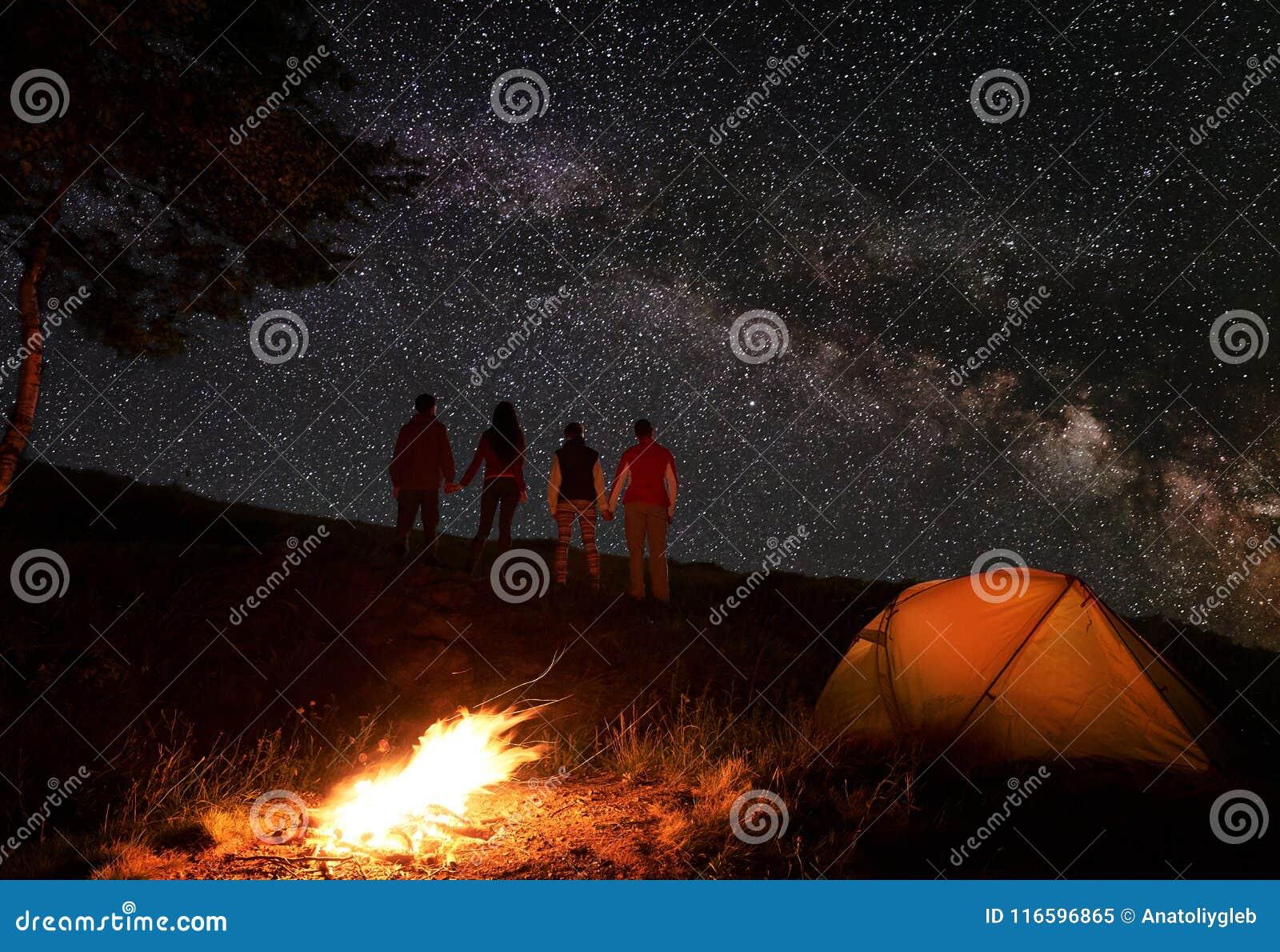 Tillbaka sikt av två händer och att tycka om för parinnehav den mjölkaktiga vägen på stjärnklar himmel under natt av att campa