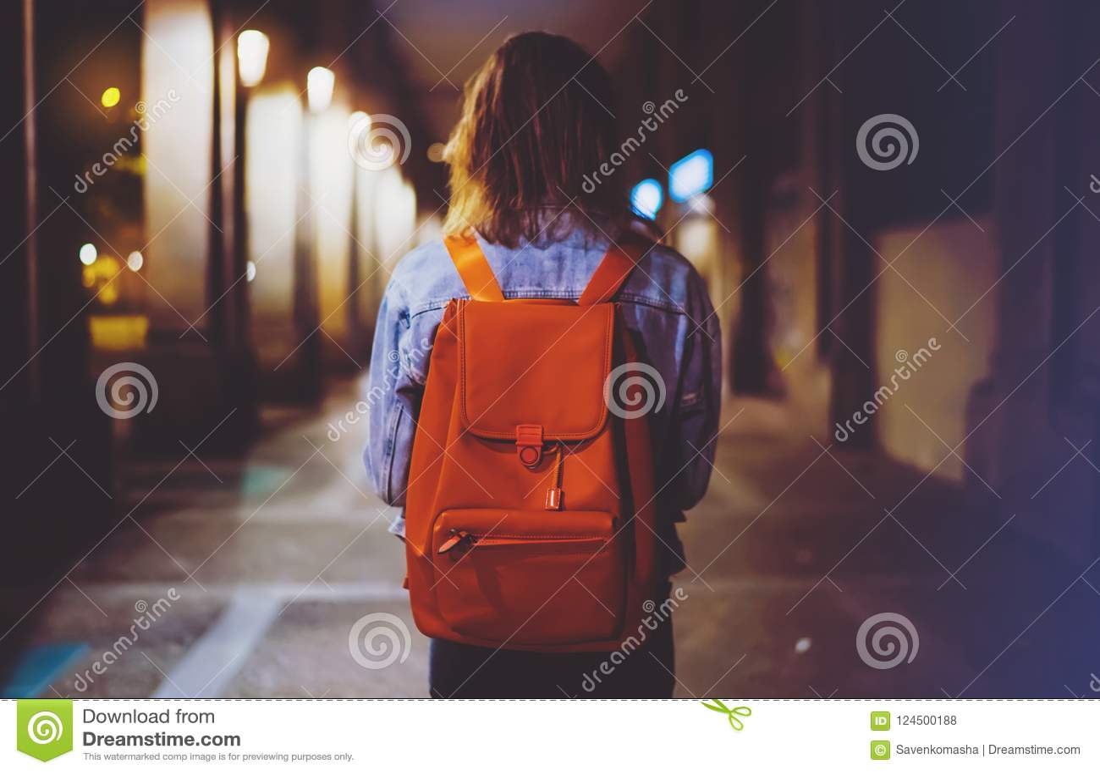 Tillbaka siktskvinna med ryggsäcken på bakgrundsbokehljus i atmosfärisk stad för natt, bloggerhipster som hyvlar ferieloppet, mod