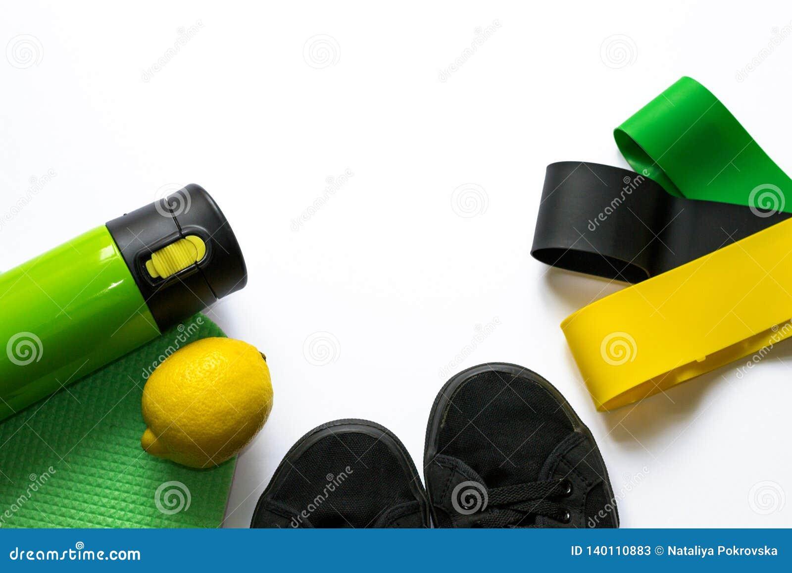 Tillbehör för utbildande execises och att förlora vikt på vit bakgrund med copyspace i gröna färger Begrepp av genomköraren, kond