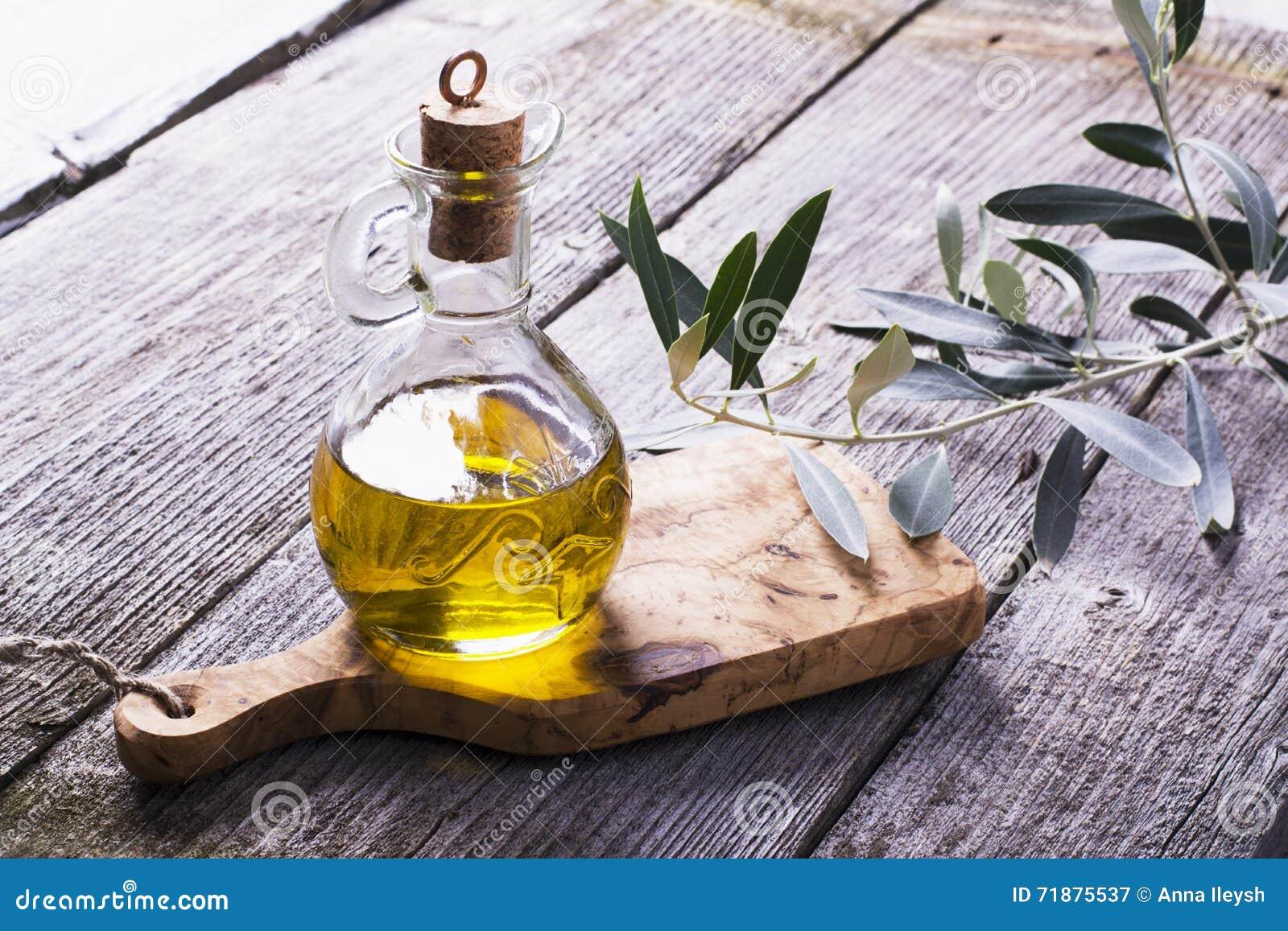 Tillbringare med extra jungfrulig olivolja på skärbrädan som omges av filialer
