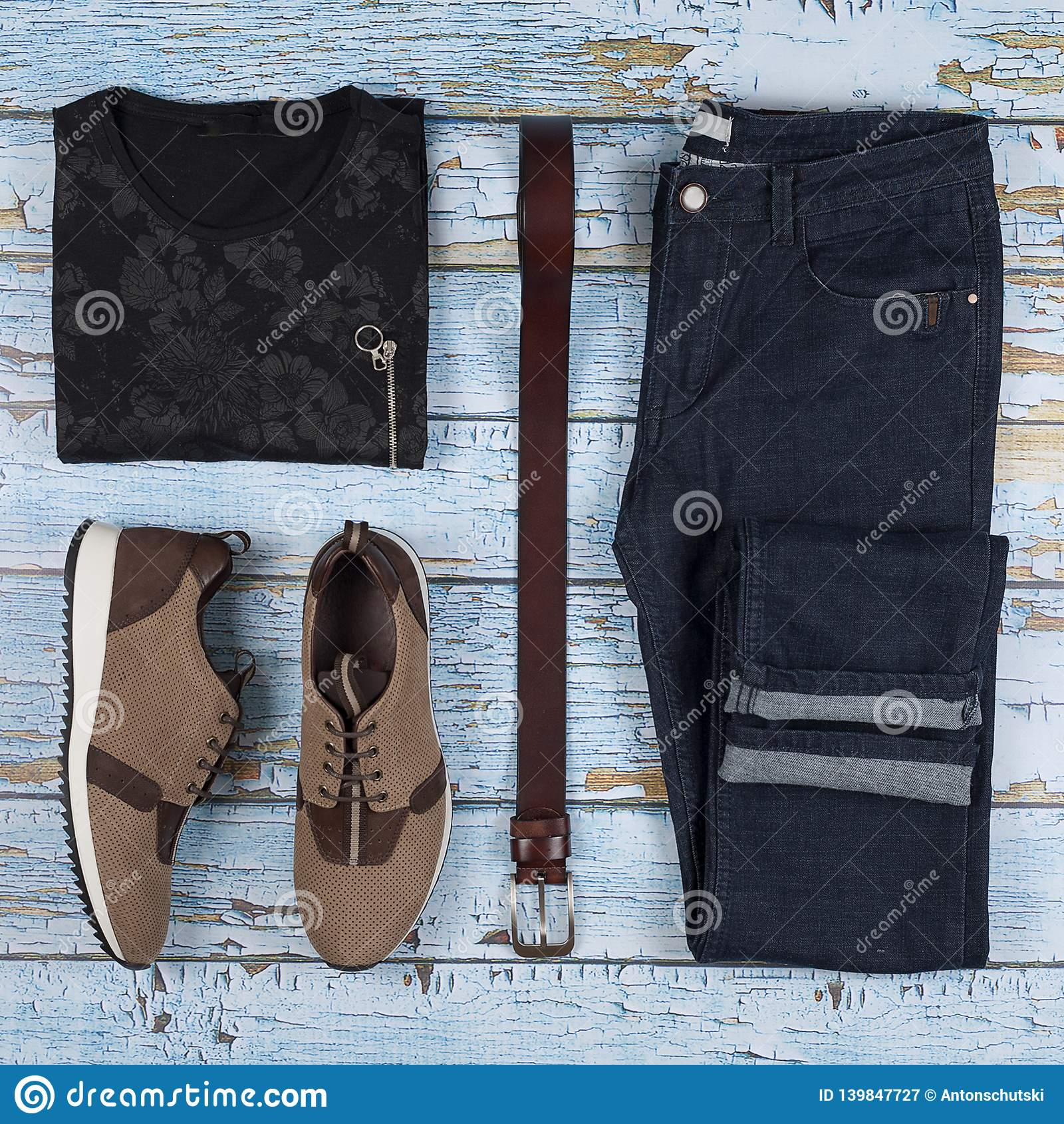 Tillfälliga dräkter för man` s Manskor, kläder och tillbehör på träbakgrund - t-skjorta, jeans, gymnastiksko, bälte Top beskådar