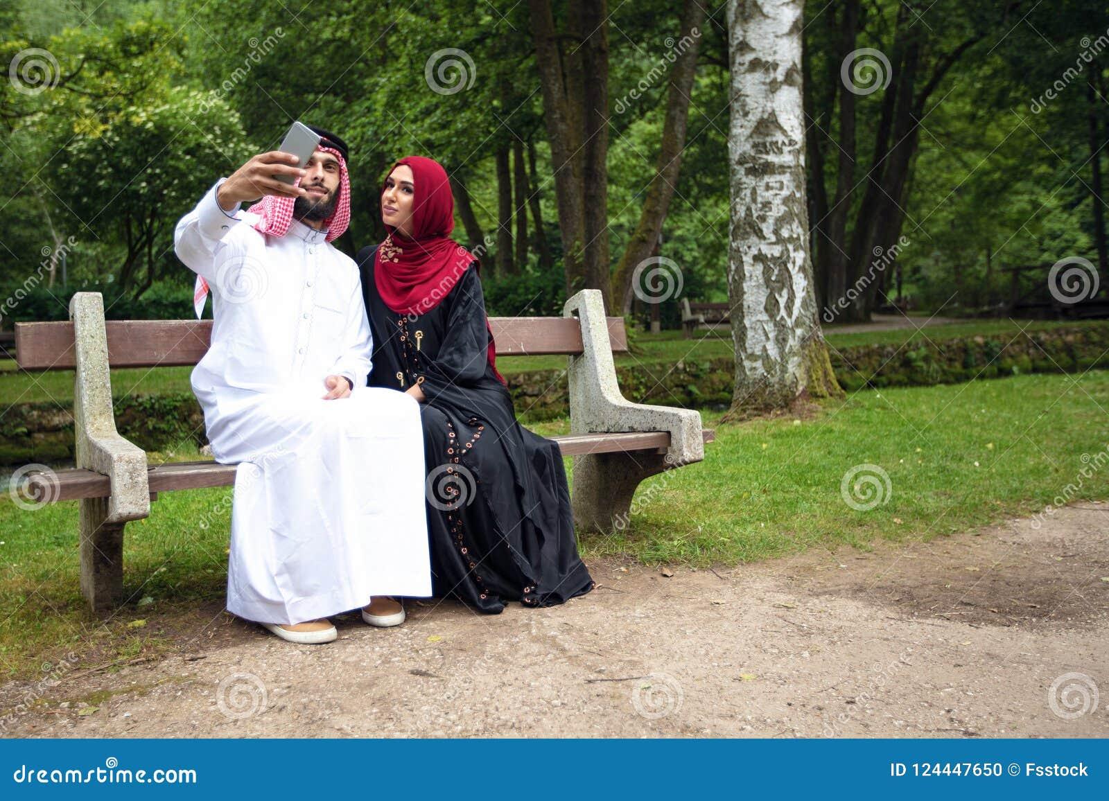 Tillfälliga unga härliga arabiska par och hijab, Abaya som tar en selfie på gräsmattan i sommar, parkerar