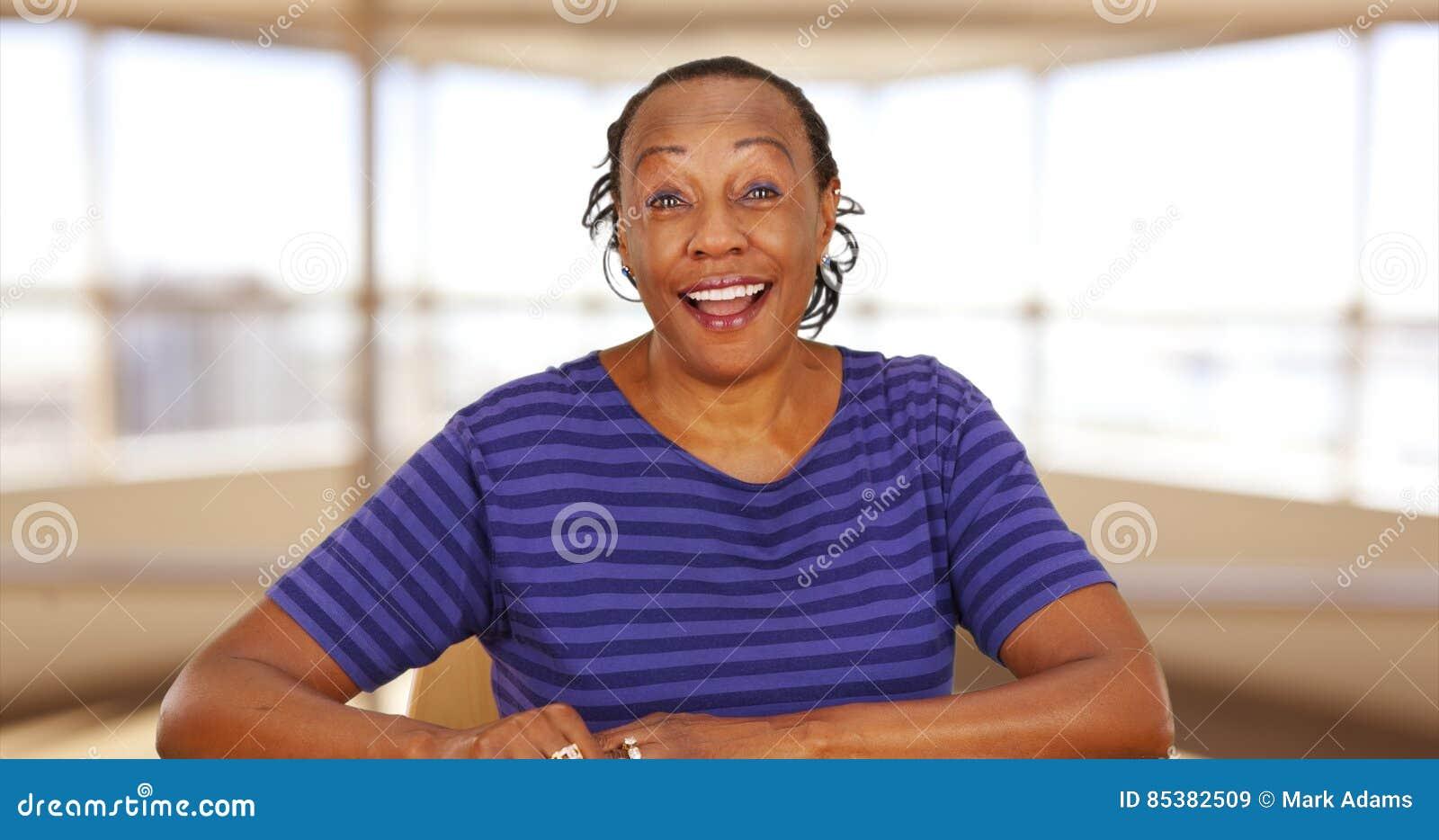 Tillfälligt en svart affärskvinna för påklädd som ler på kameran