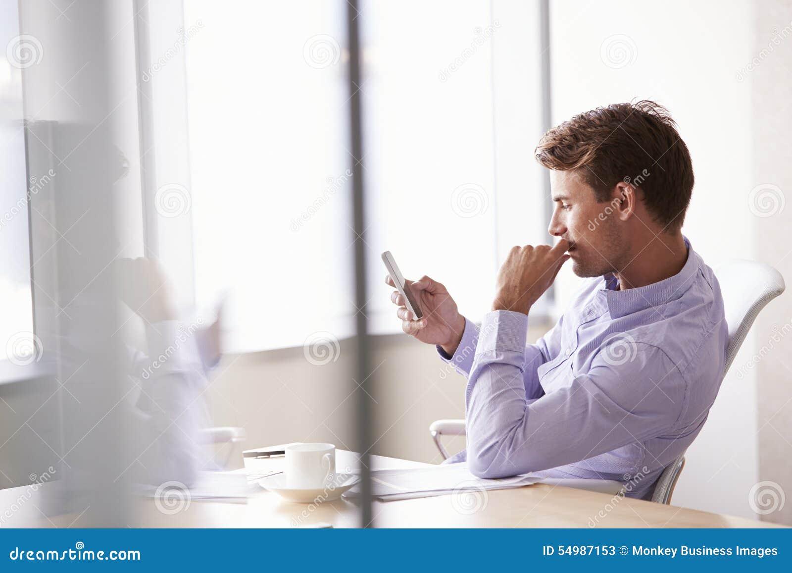 Tillfälligt klädd affärsman Using Mobile Phone i regeringsställning