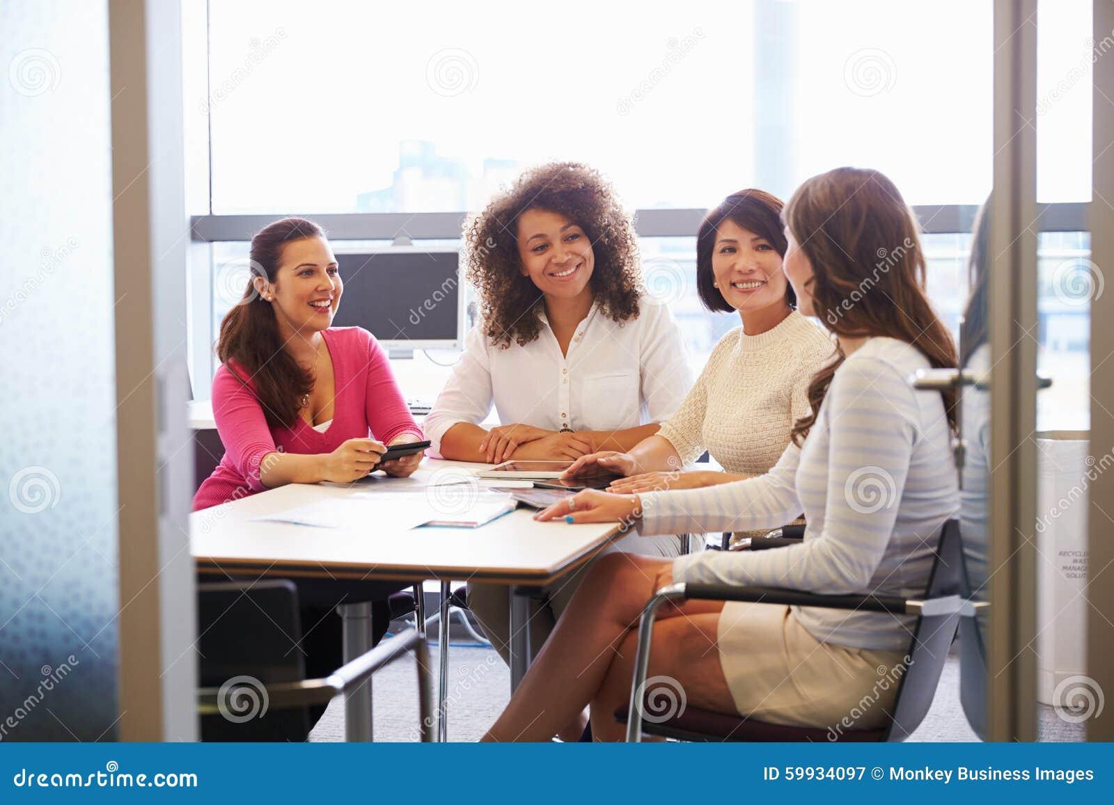 Tillfälligt klädda kvinnliga kollegor som talar i en mötesrum