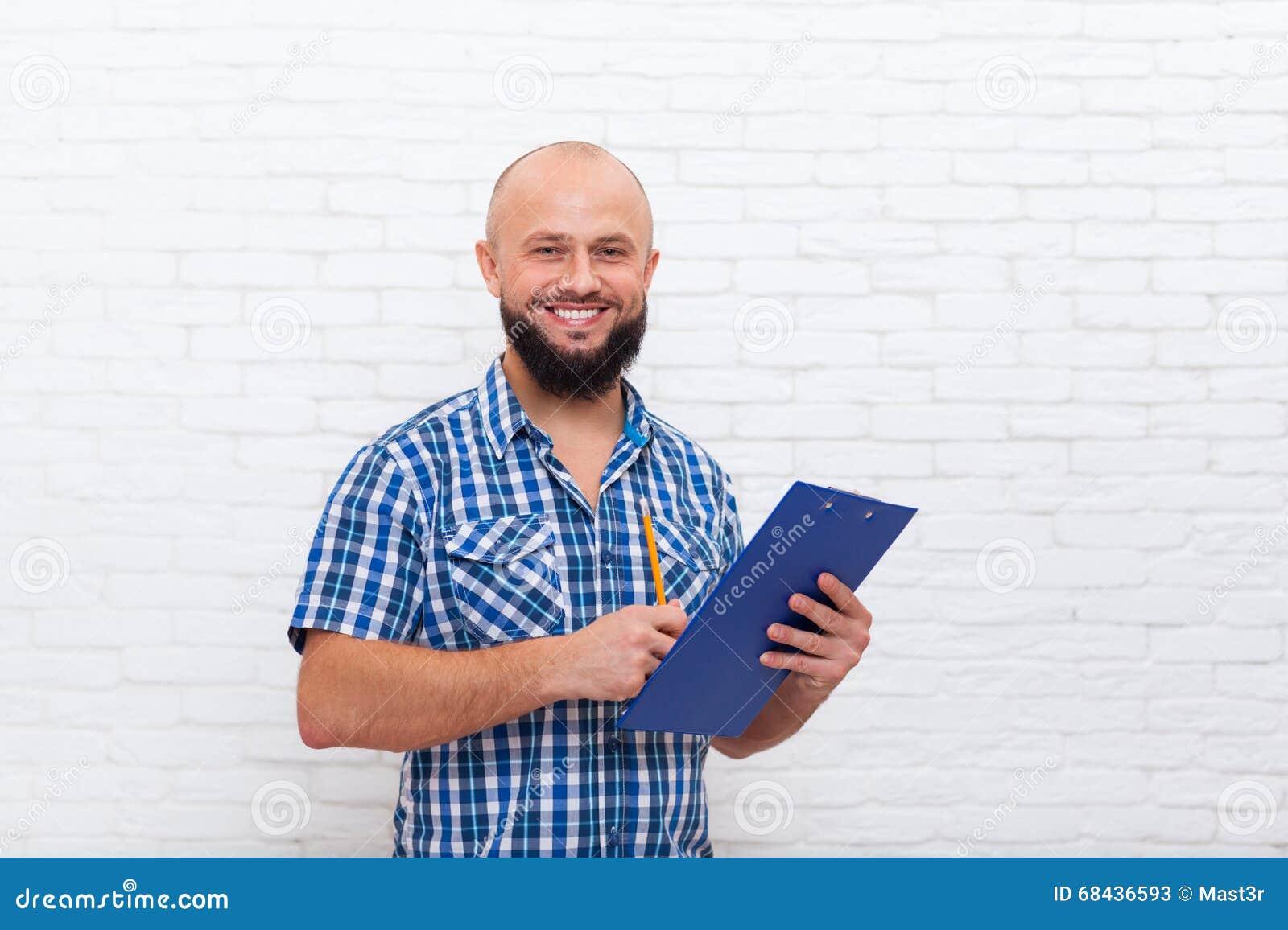 Tillfälligt skäggigt dokument för blyertspenna för mapp för affärsman som hållande skriver lyckligt leende