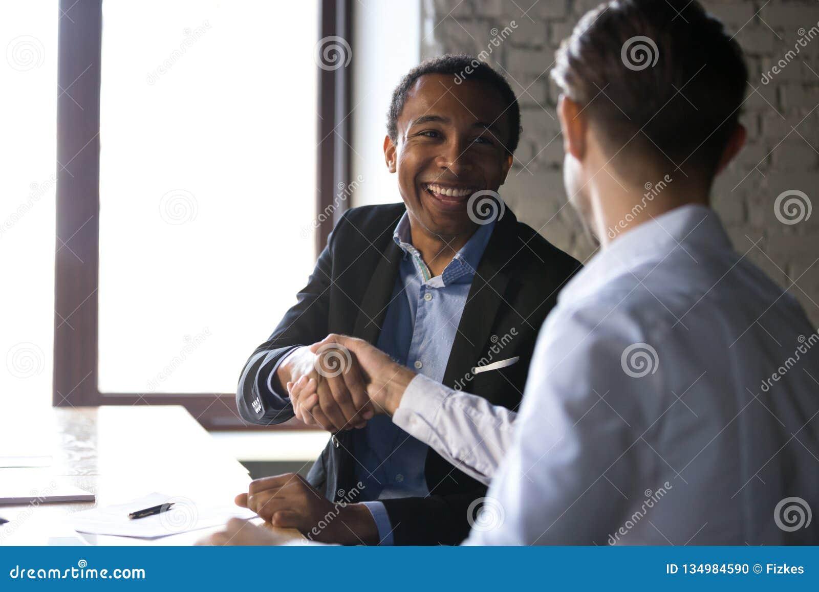 Tillfredsställd svart klient som skakar händer som tackar chefen för bra D
