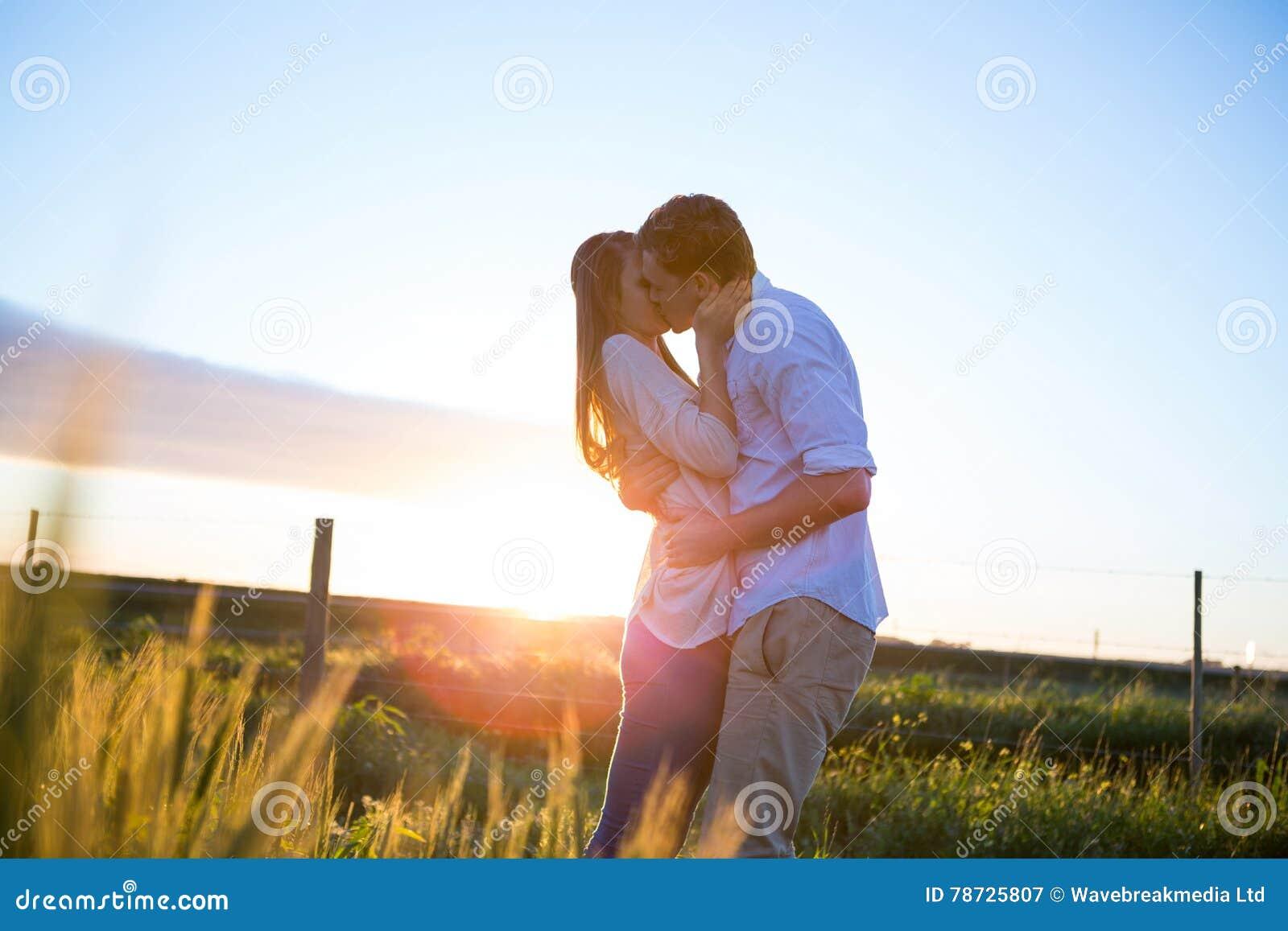 Tillgivna par som kysser i fält