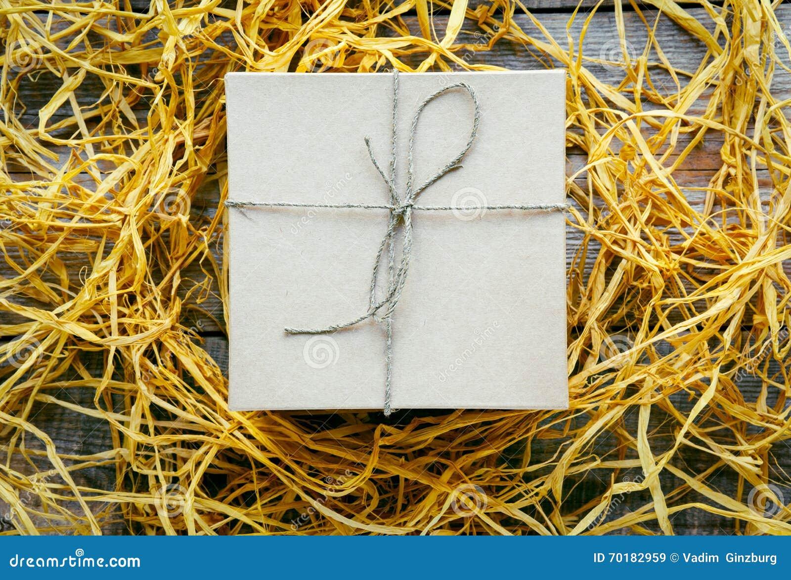 Tillverka gåvaasken på trätabellen med basten eller tvinna