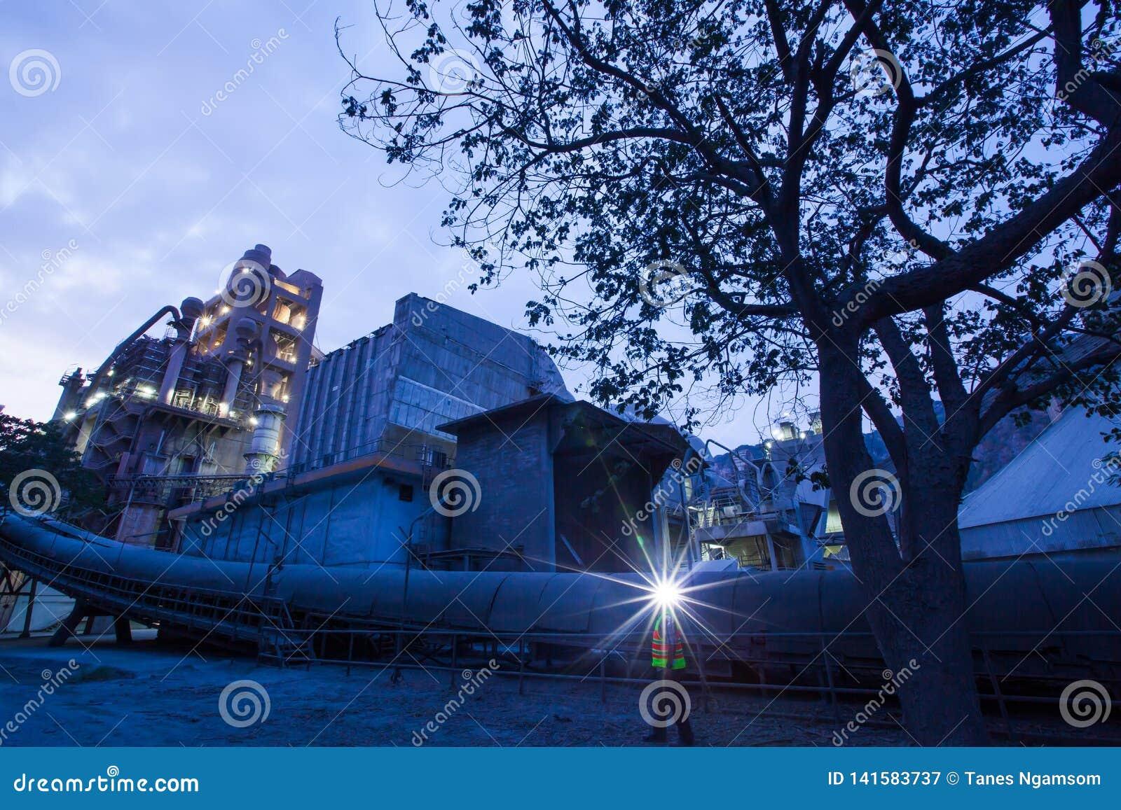 Tillverkning för cementväxtfabrik på skymning, gnistor av arbetaren med pannlampaficklampan under arbetande övertid