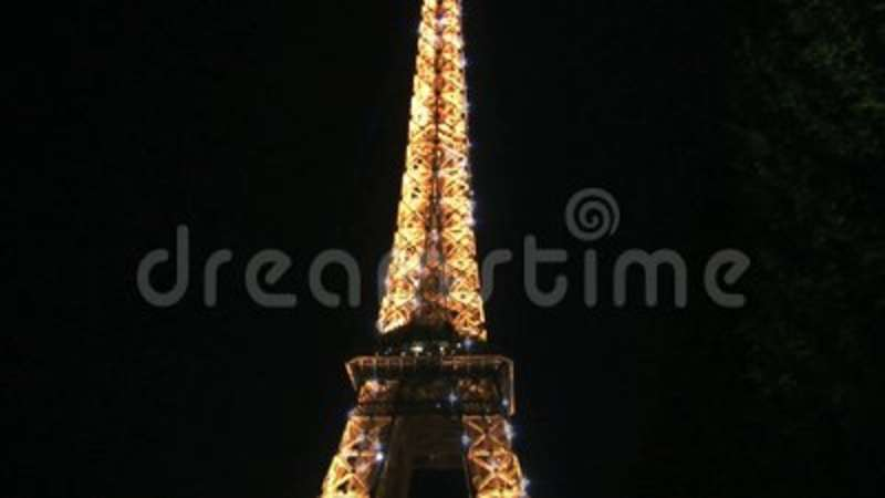 tilt up from the eiffel tower at night with sparkling lights stock