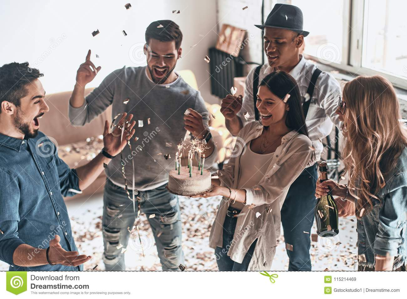 Time for a birthday cake. Top view of happy young man celebrating birthday among friends while standing in room with confetti fly