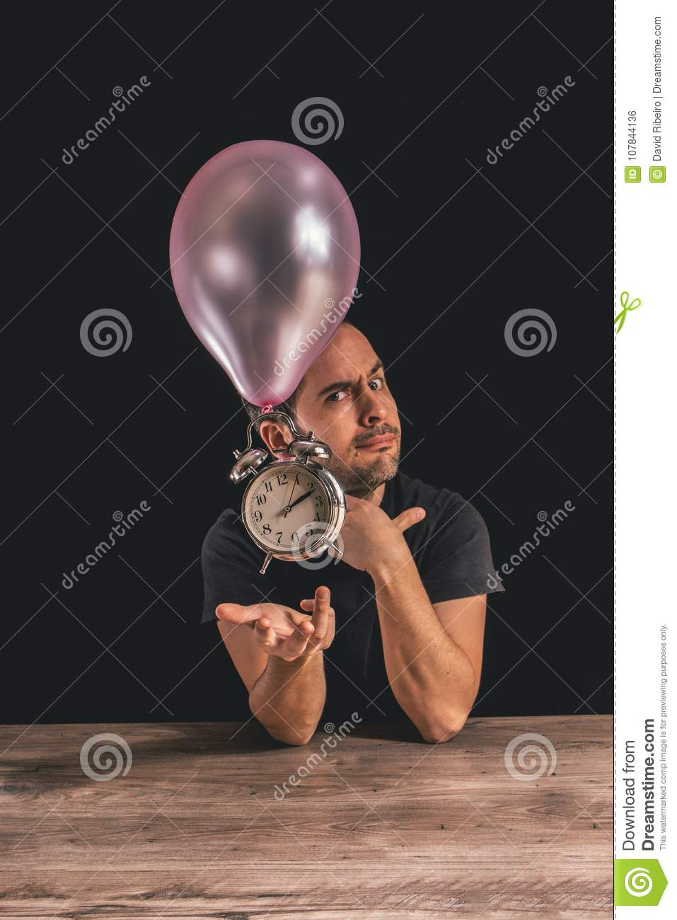 Time flies concept - picture of a man looking at the camera while placing his hand underneath an old metal clock