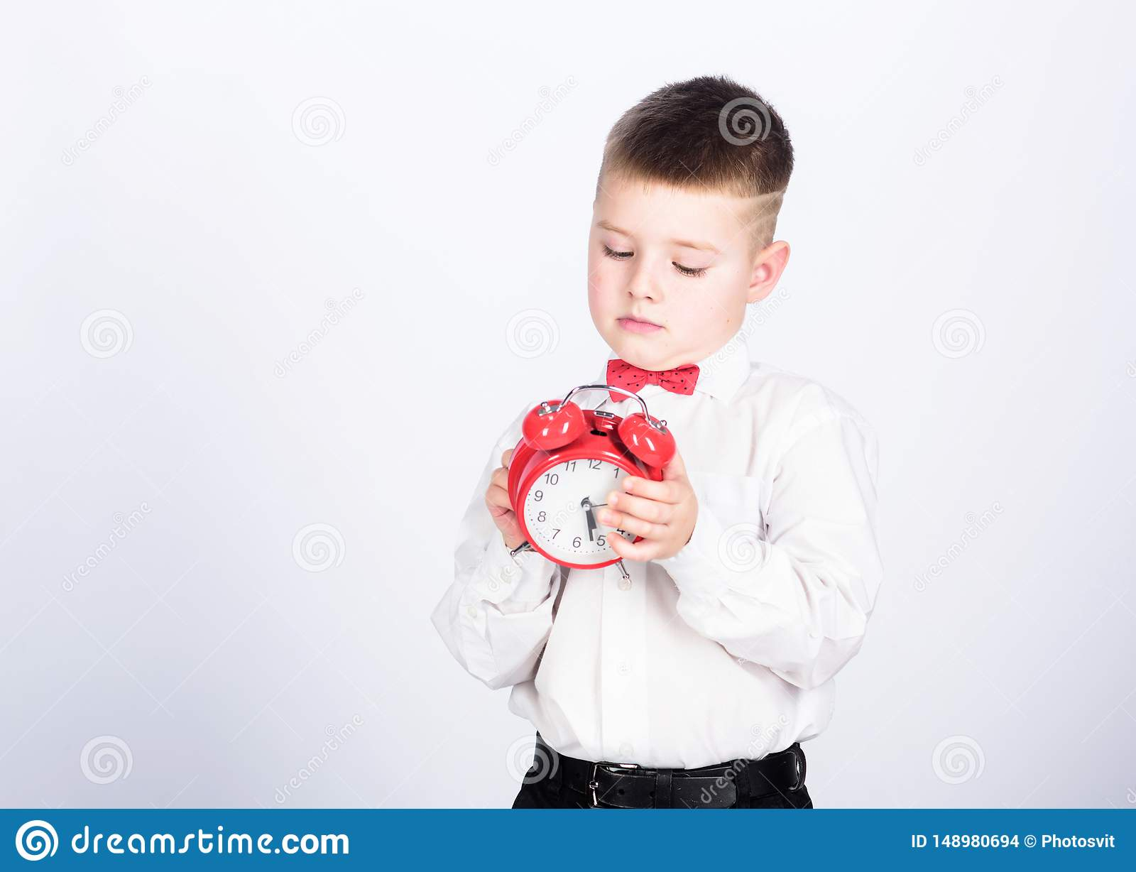 It is time. Schedule and timing. Morning routine. Schoolboy with alarm clock. Kid adorable boy white shirt red bow tie