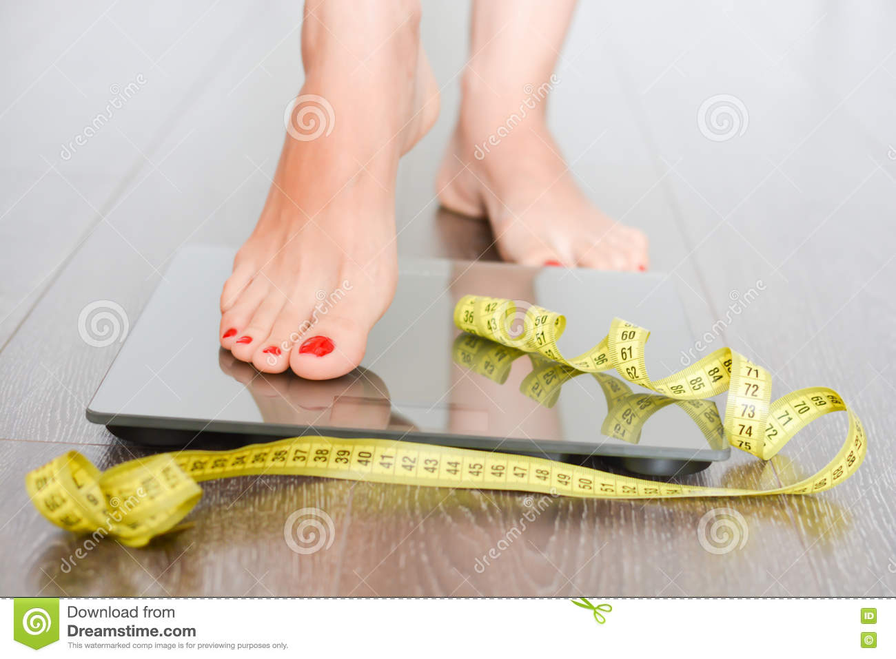 Time to lose kilograms with woman feet stepping on a weight scale