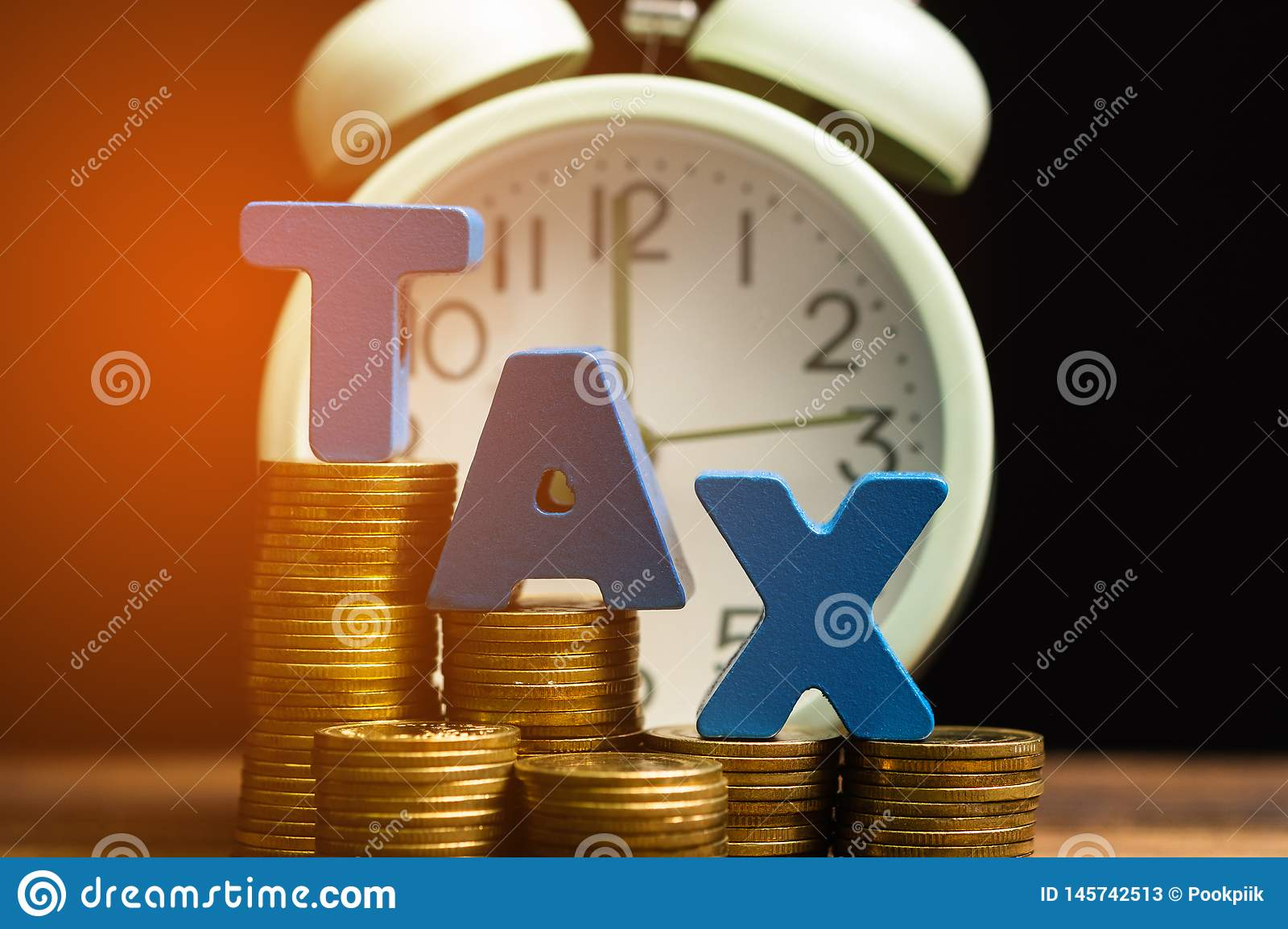 Time to pay TAX concept. TAX alphabet with stack of coin and vintage alarm clock on wooden working table in dark background,