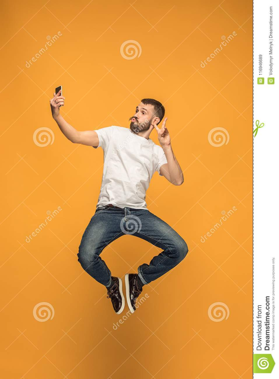 Time to take selfie. Full length of handsome young man taking selfie while jumping