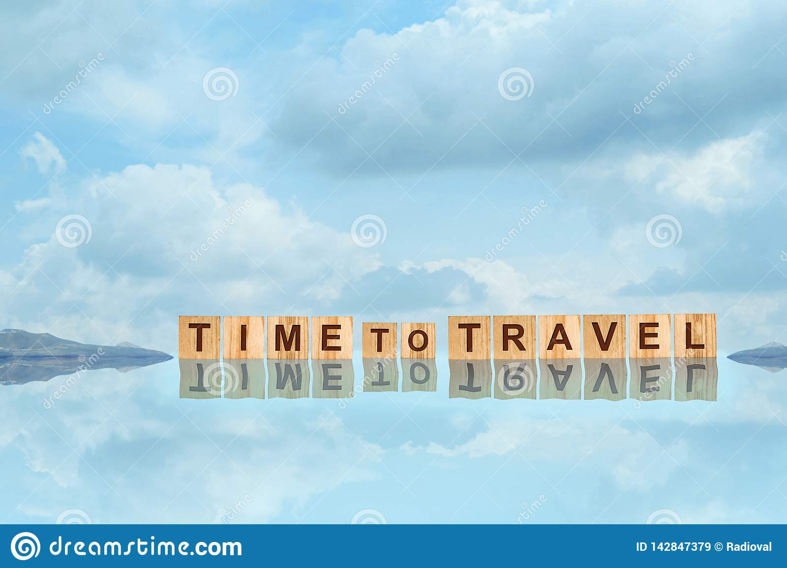 Time To Travel word written on wooden blocks with reflection, against the blue sky with beautiful clouds. Copy space. Travel
