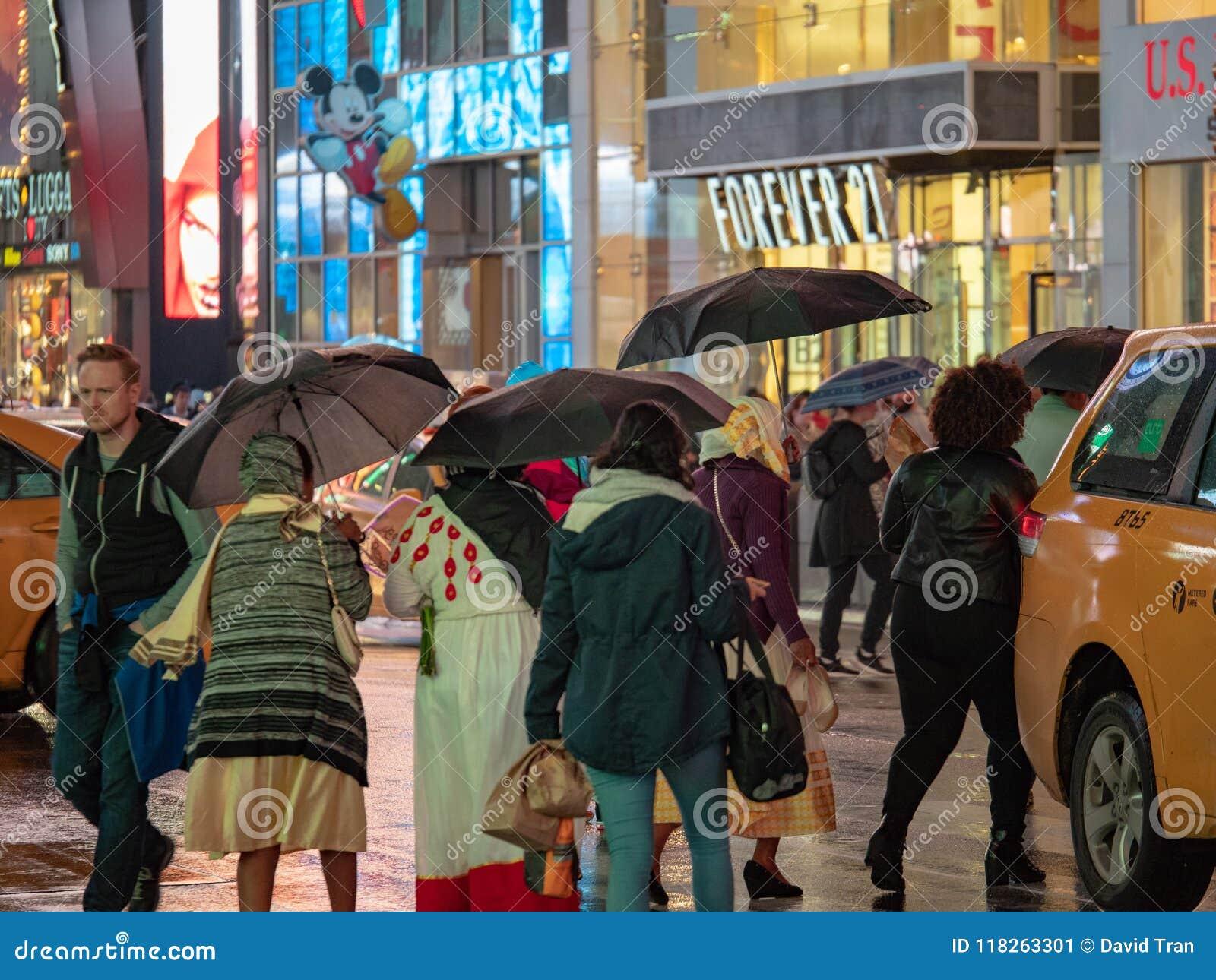 Times Square-Touristen gehen hinter Einzelhandelsgeschäfte auf einem regnerischer Taghol
