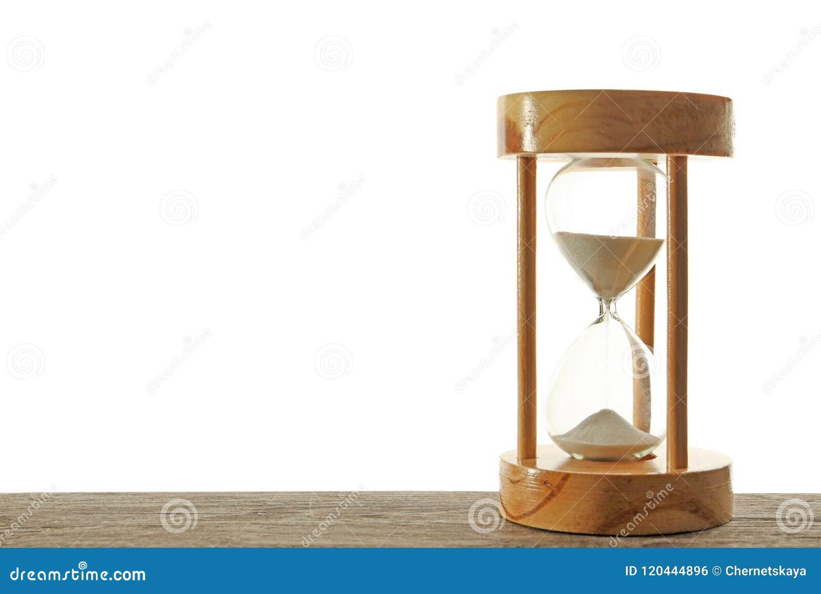 Timglas med flödande sand på tabellen mot vit bakgrund Tid ledning