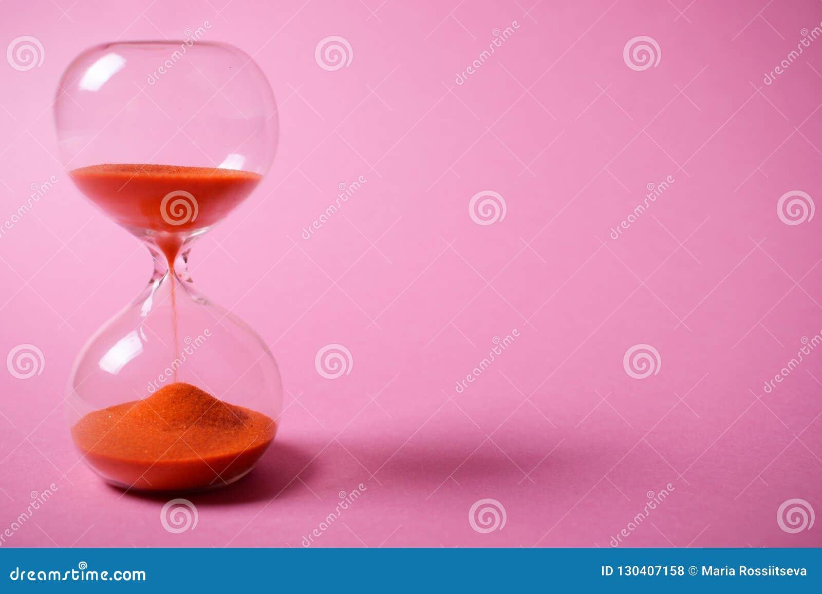 Timglas med orange sand på rosa bakgrund