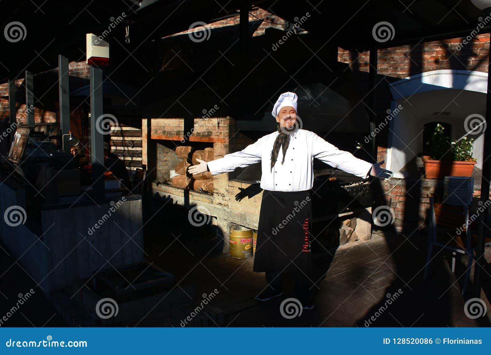 TIMISOARA, ROEMENIË 11 28 2017 kleedde een mens zich met een snor aangezien een chef-kok, die een witte cook'shoed dragen, met