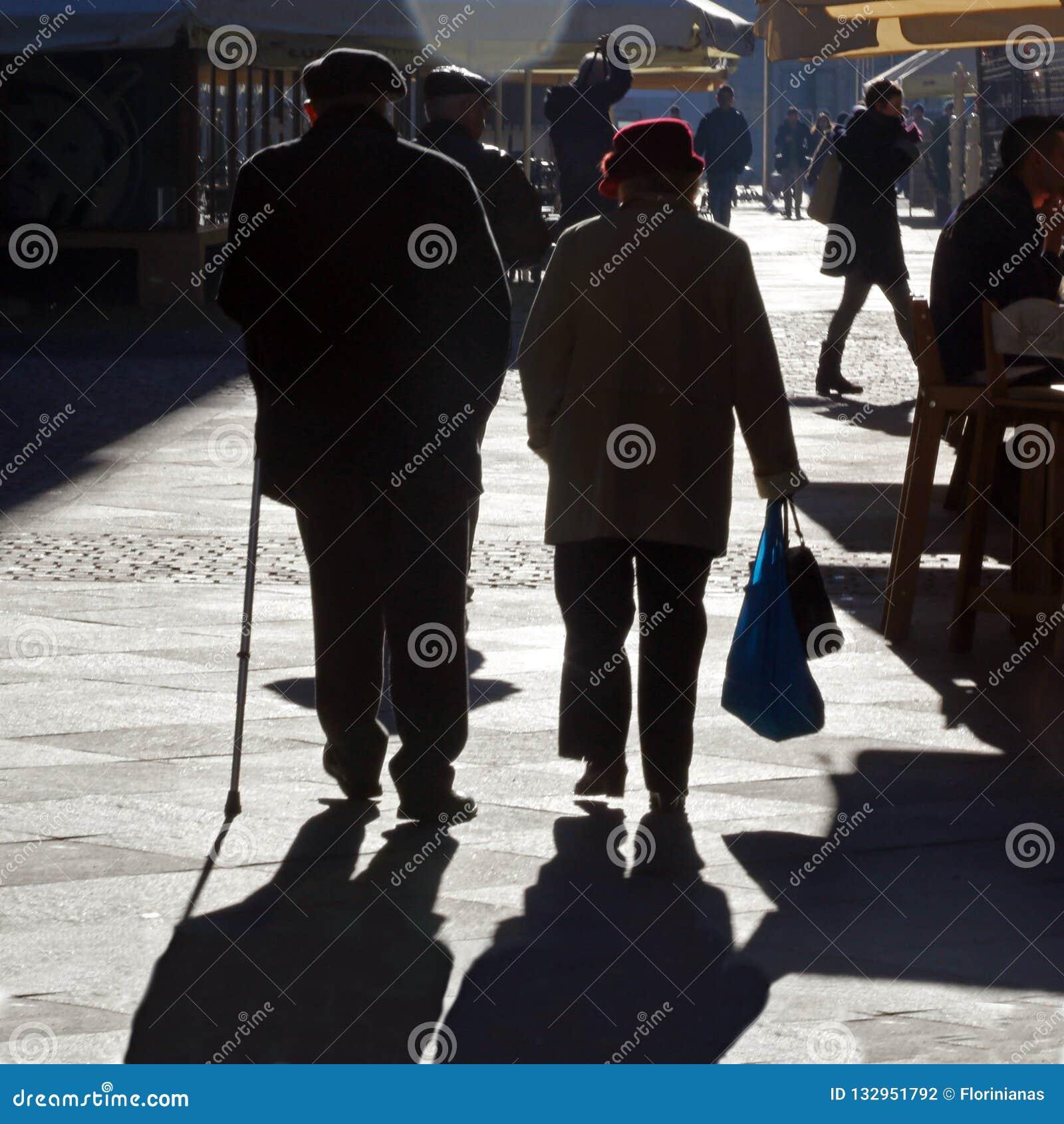 TIMISOARA, ROMANIA -12 13 Passeggiata di 2016 una vecchia coppie congiuntamente su una via nel vecchio centro urbano in luce sola