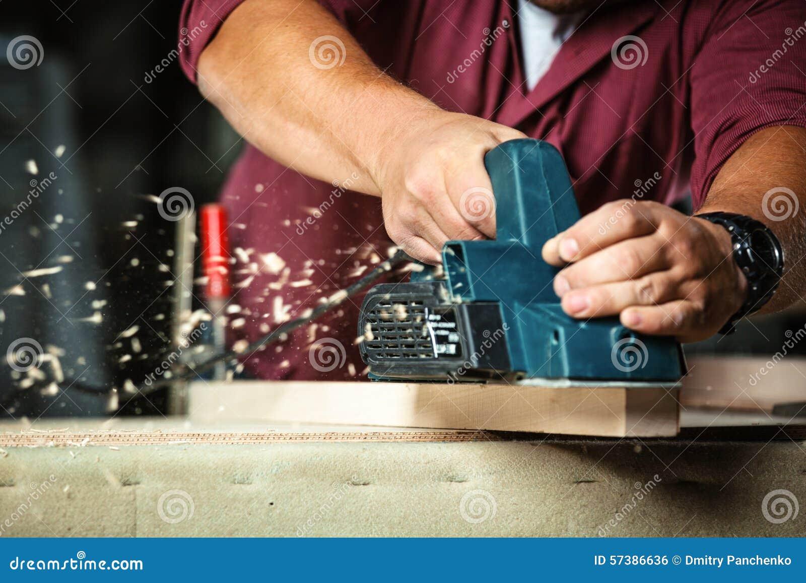 Timmerman die met elektrische planer werkt