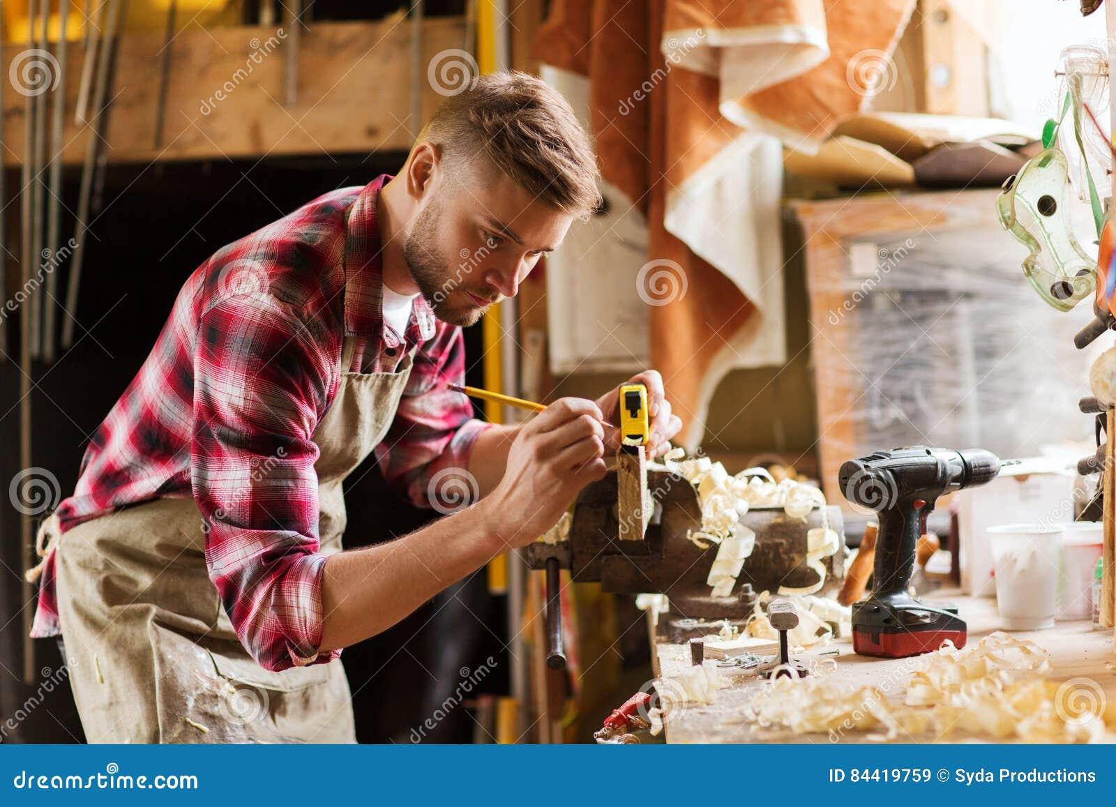 Timmerman met heerser die plank meten op workshop