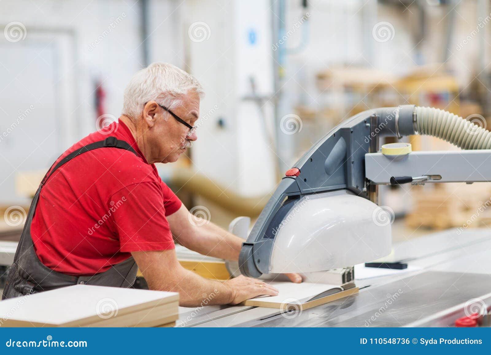 Timmerman met paneelzaag en houtvezelplaat bij fabriek