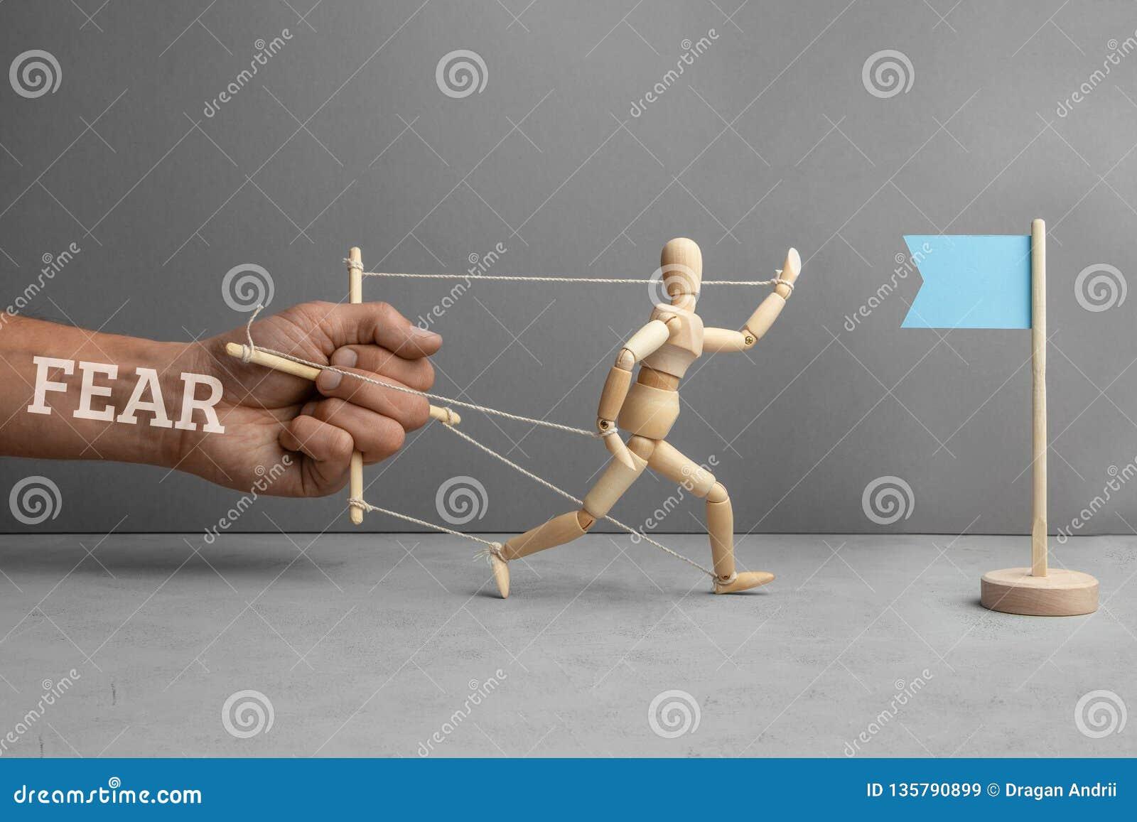 Timore degli ostacoli sul modo allo scopo Il timore come burattinaio tiene la bambola e non lo lascia andare alla bandiera come s