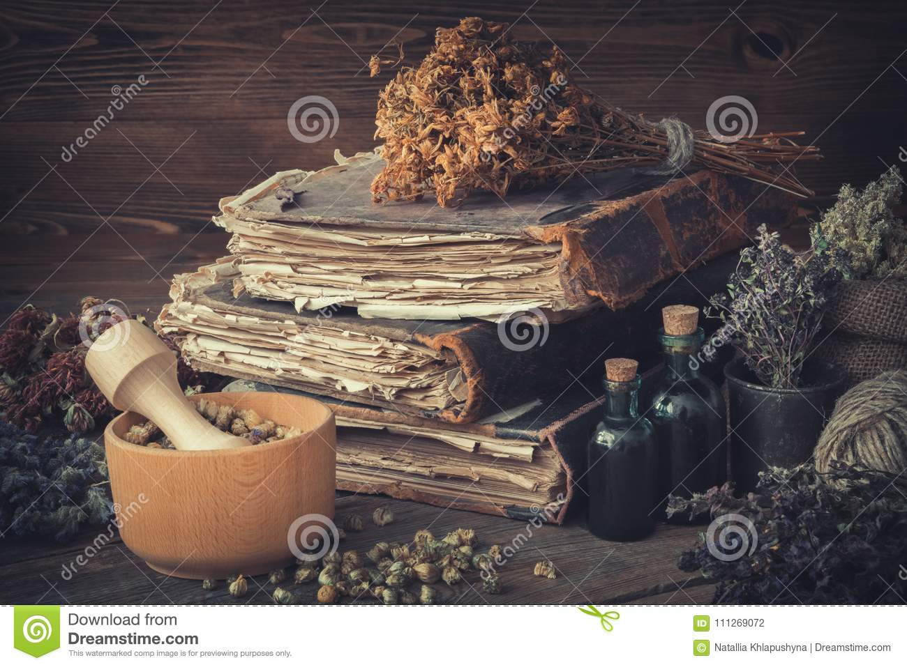 Tincture bottles, bunches of healthy herbs, stack of antique books, mortars, sack of medicinal herbs. Herbal medicine.