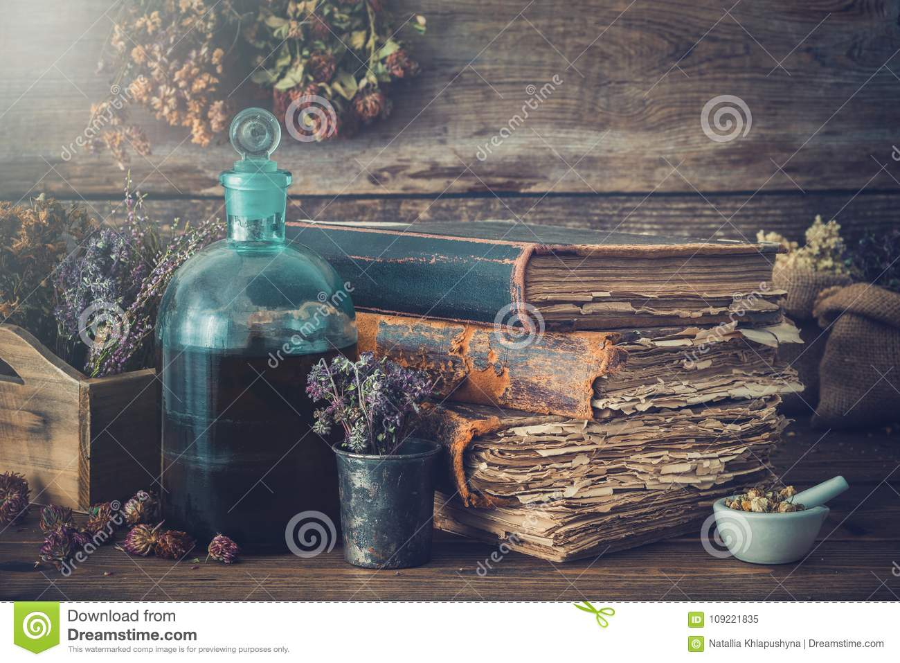 Tincture bottles, dry healthy herbs, old books, mortar, curative drugs. Herbal medicine.