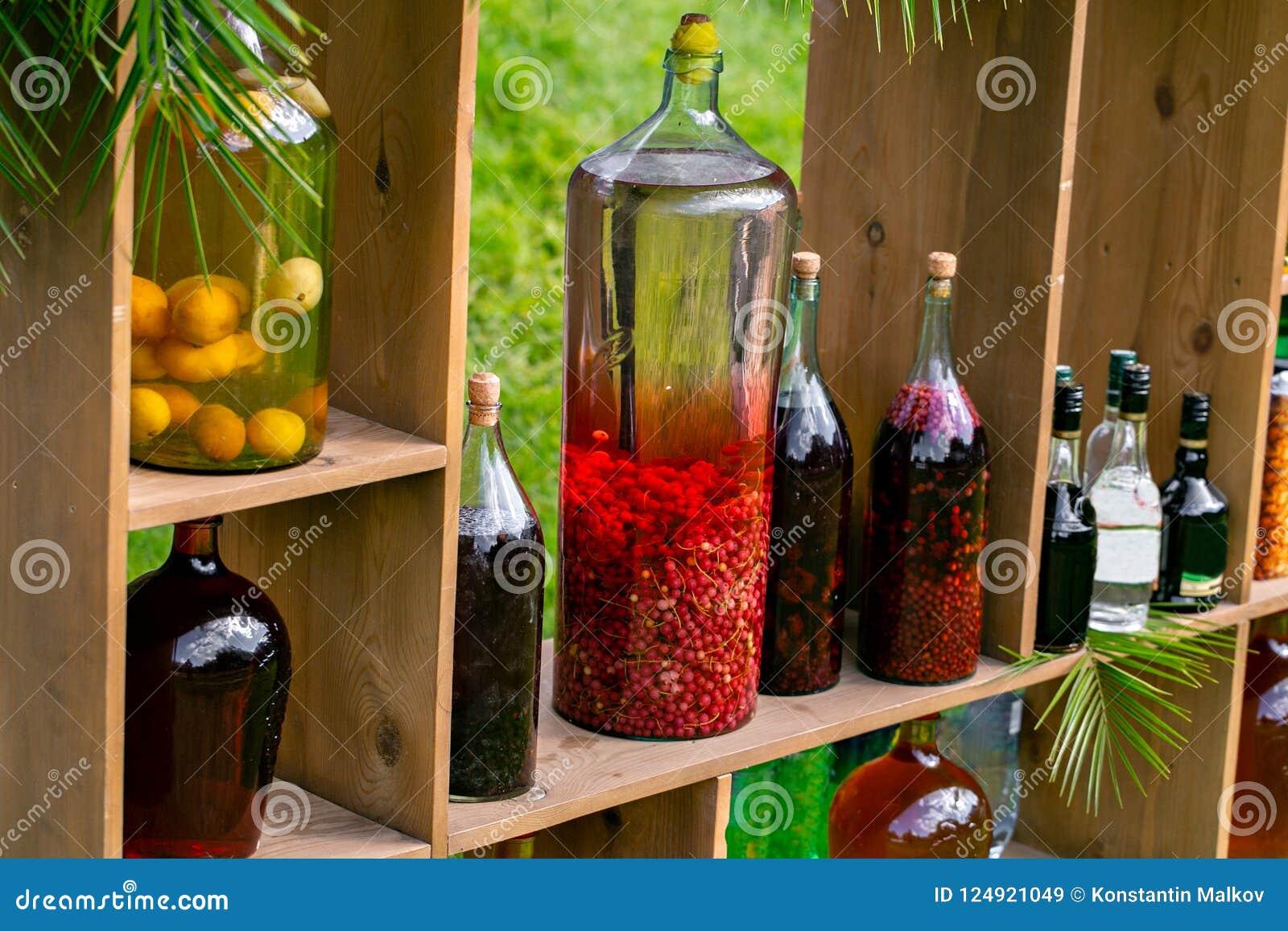 Tincture bottles of lemon, currant, berries and rowanberries. Herbal medicine. Spirits, wine and liqueur