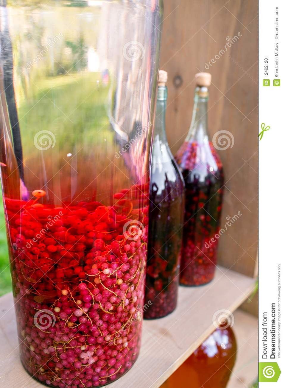 Tincture bottles of lemon, currant, berries and rowanberries. Herbal medicine. Spirits, wine and liqueur