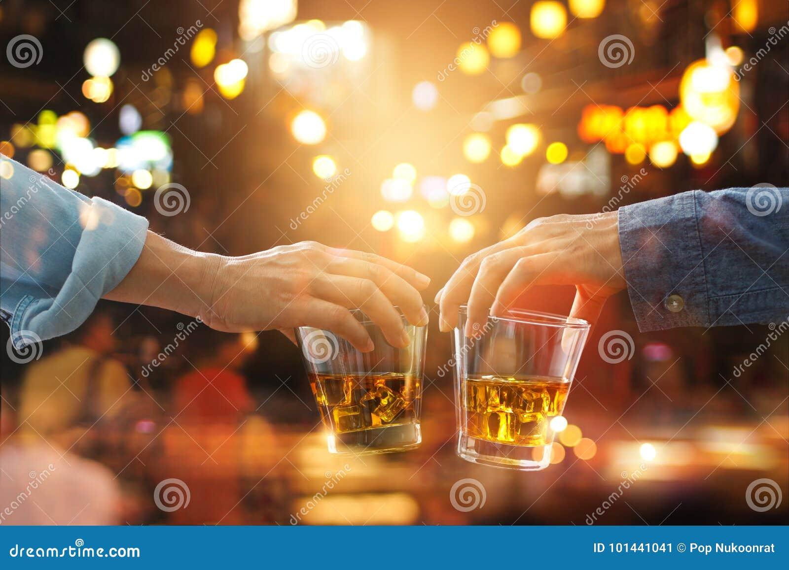Tinido dos elogios dos amigos com bebida do uísque de bourbon no partido