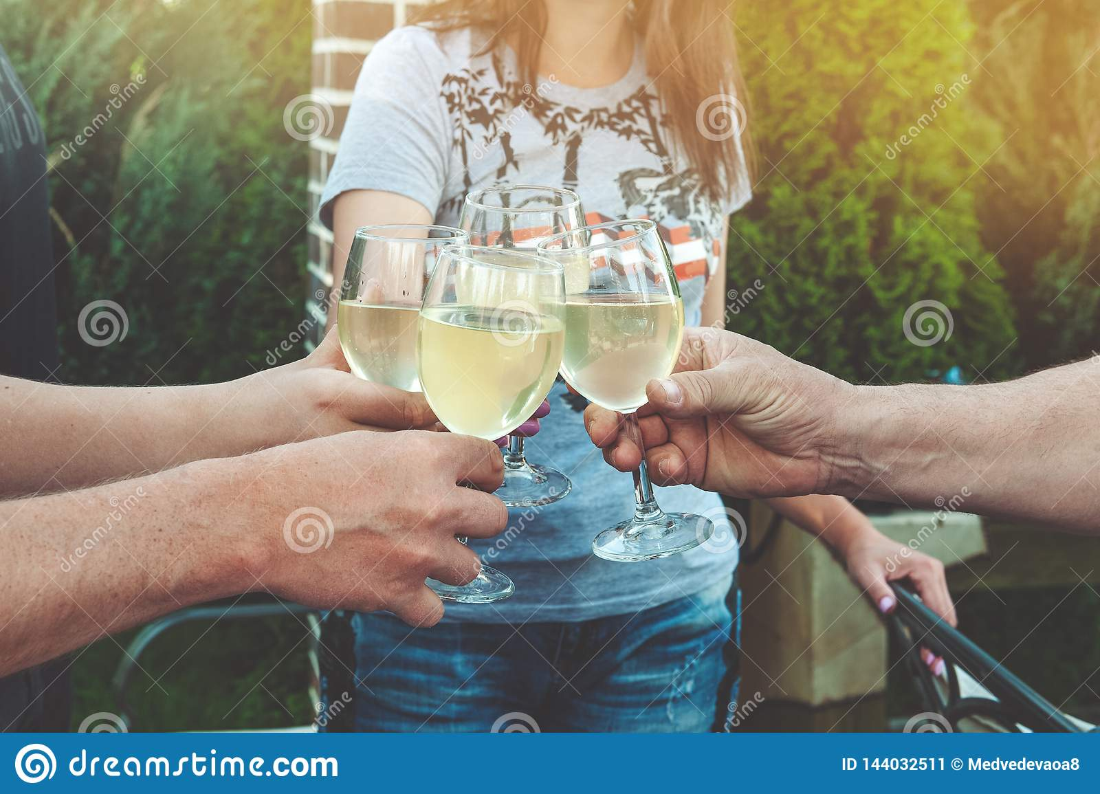 Tinkling glasses of white wine and toast. Young people celebrate a birthday at a picnic