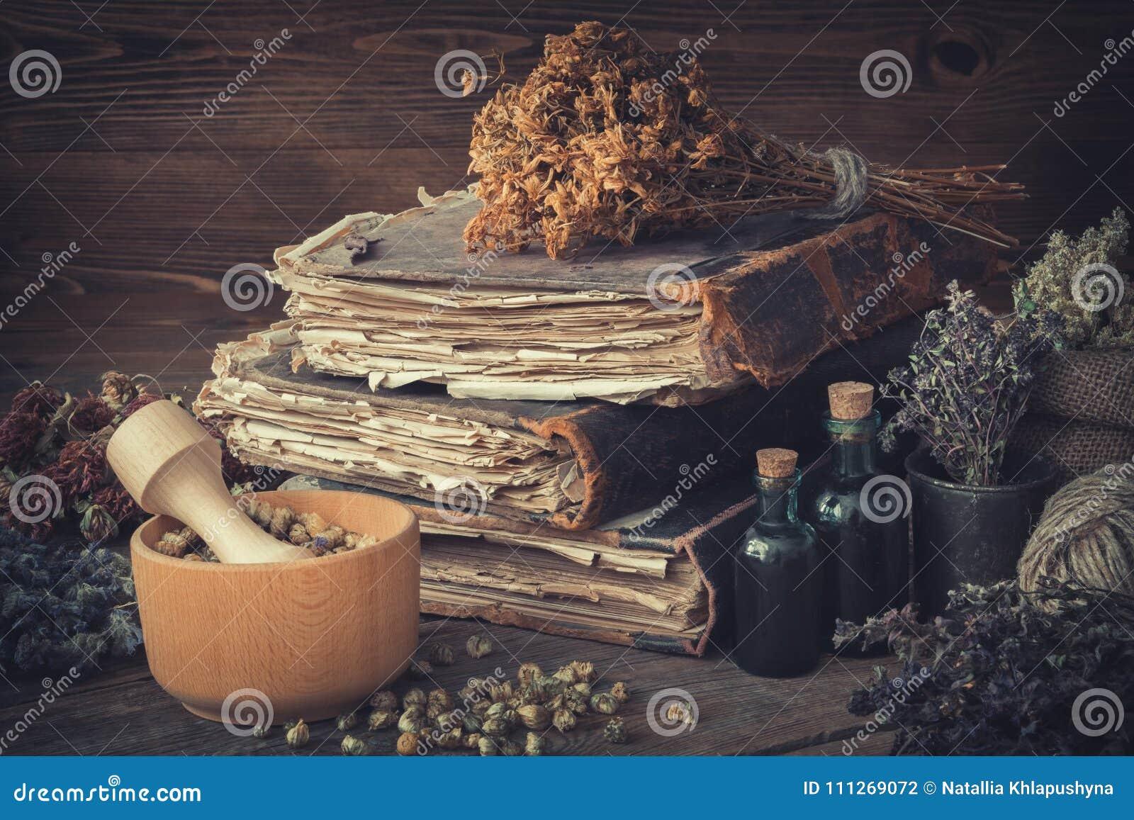 Tinktur buteljerar, samlar ihop av sunda örter, bunt av antikvitetböcker, mortlar, säcken av medicinska örter som behandling för