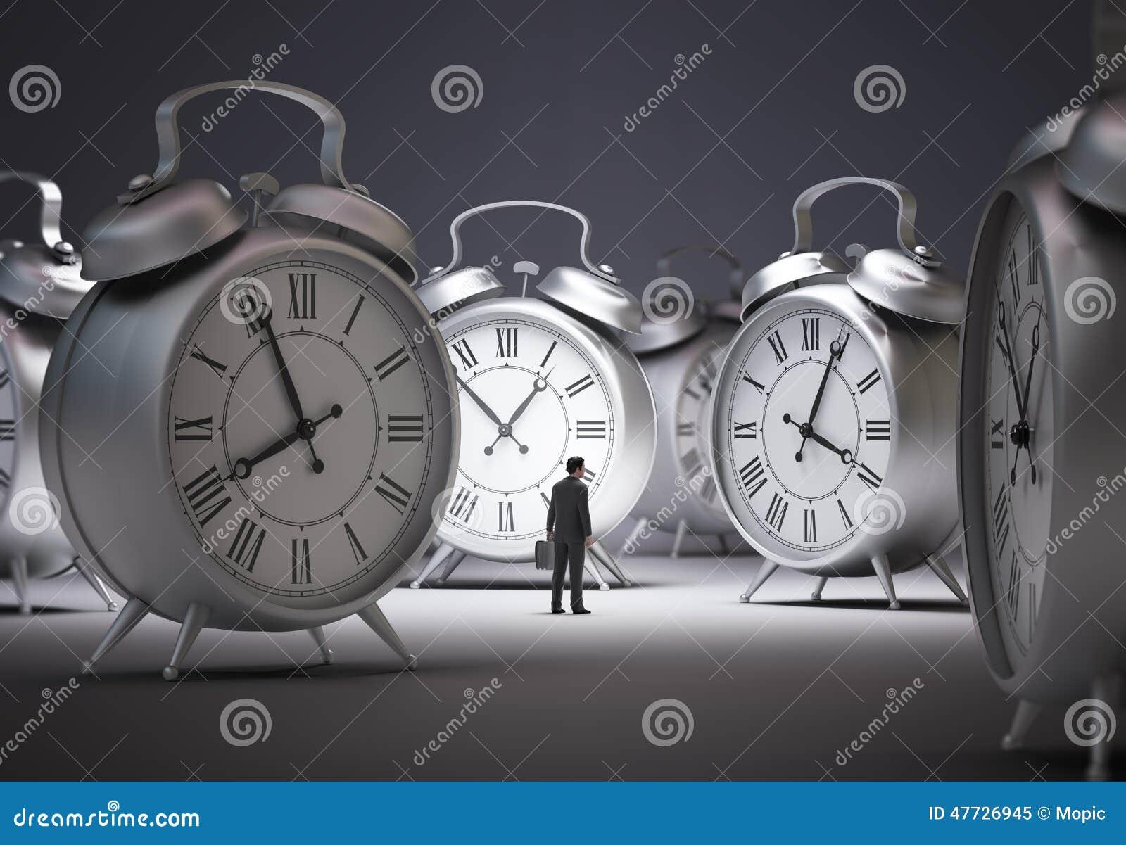 Tiny businessman with alarm clocks