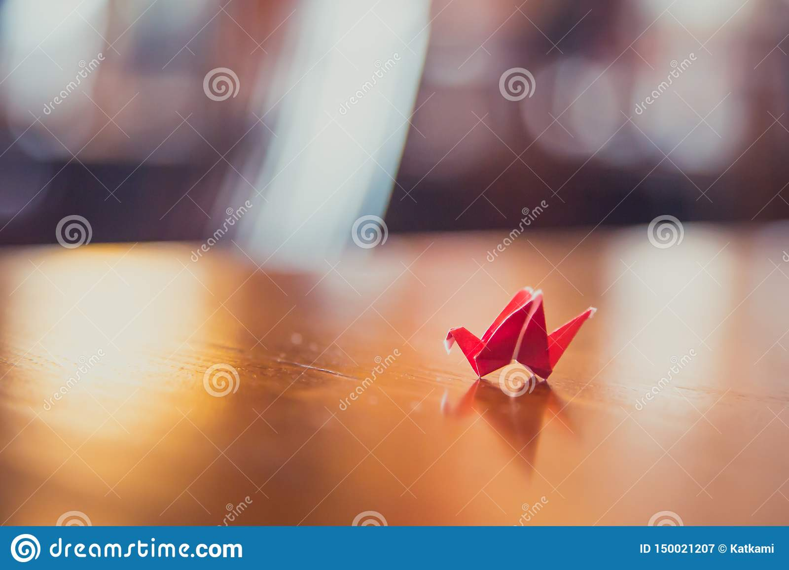 Tiny red origami crane on table