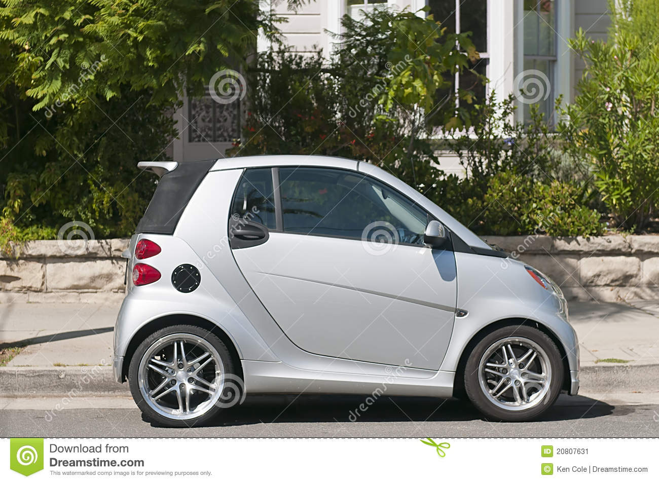 tiny, silver, subcompact Smart Car, parked on a residential street.