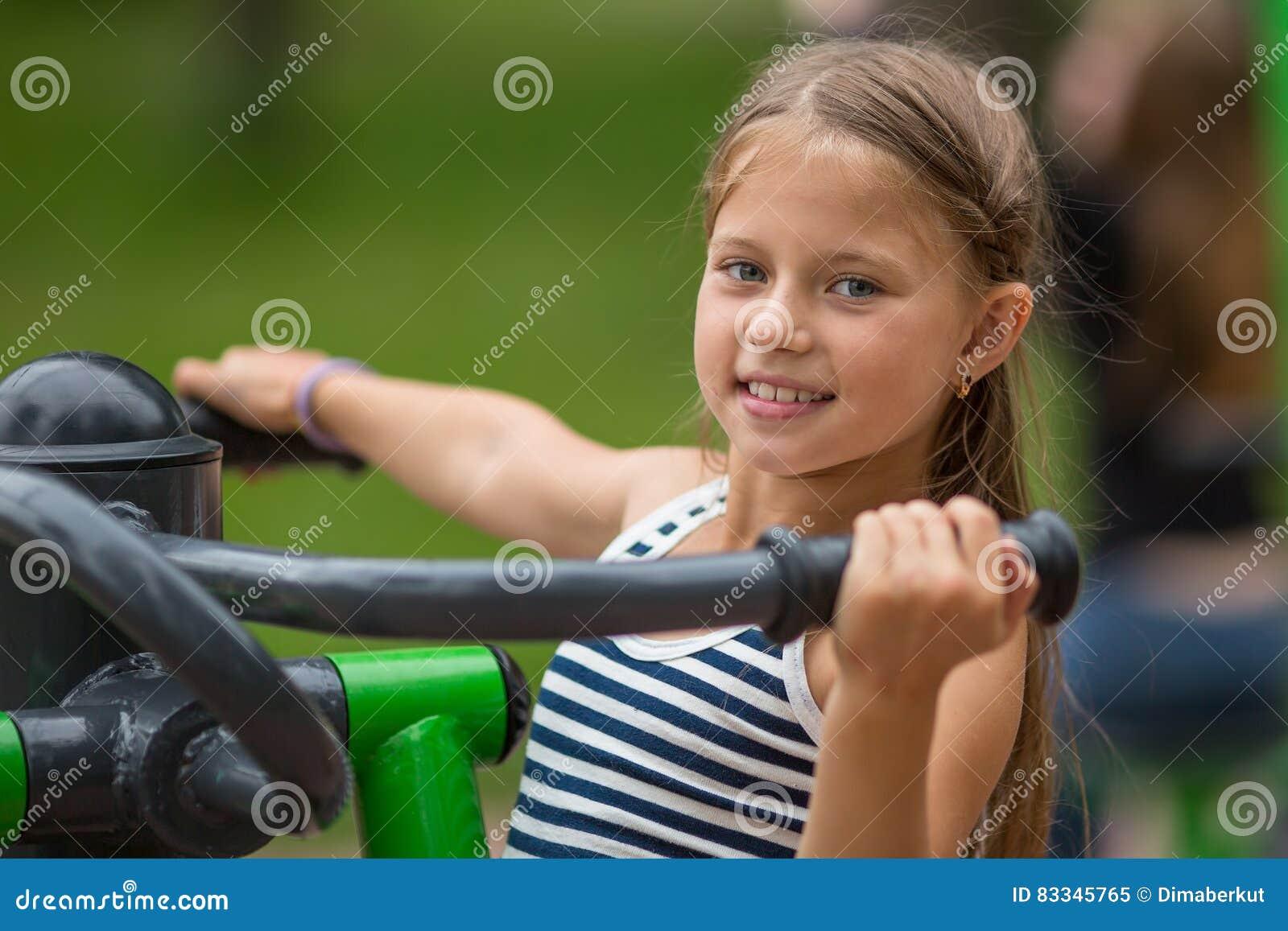 Tio-året flickan som gör övningar på sportar, grundar utomhus