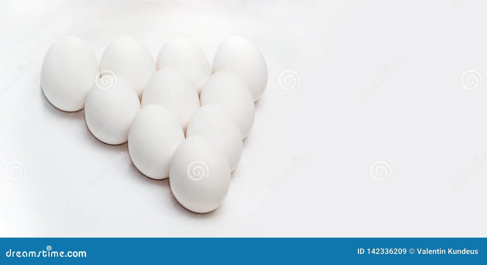Tio vita ägg på en vit bakgrund i form av en triangel sund mat Sund livsstil Protein och äggula i skalet