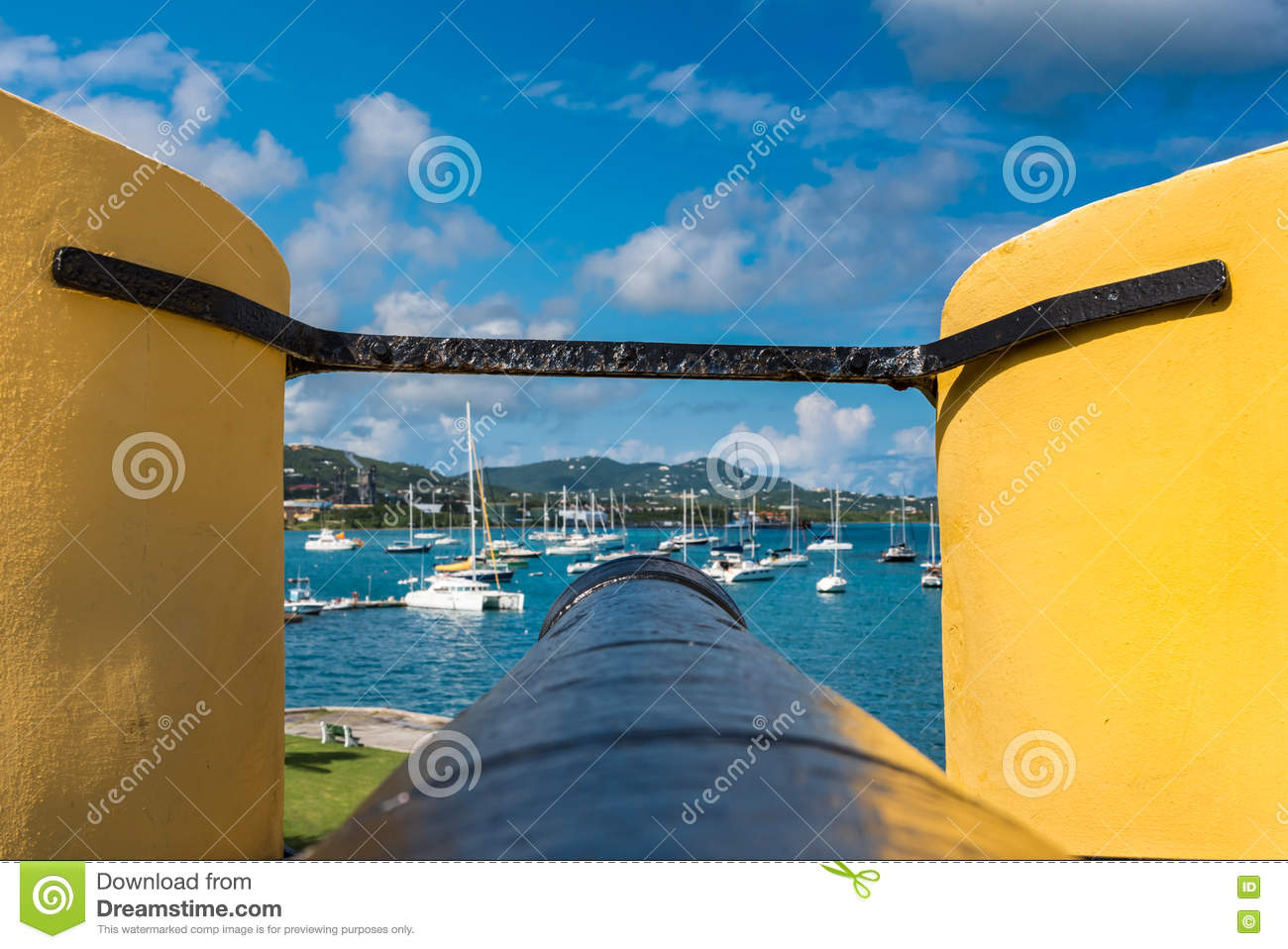 Tip of a vintage cannon through the turret facing the sailboats