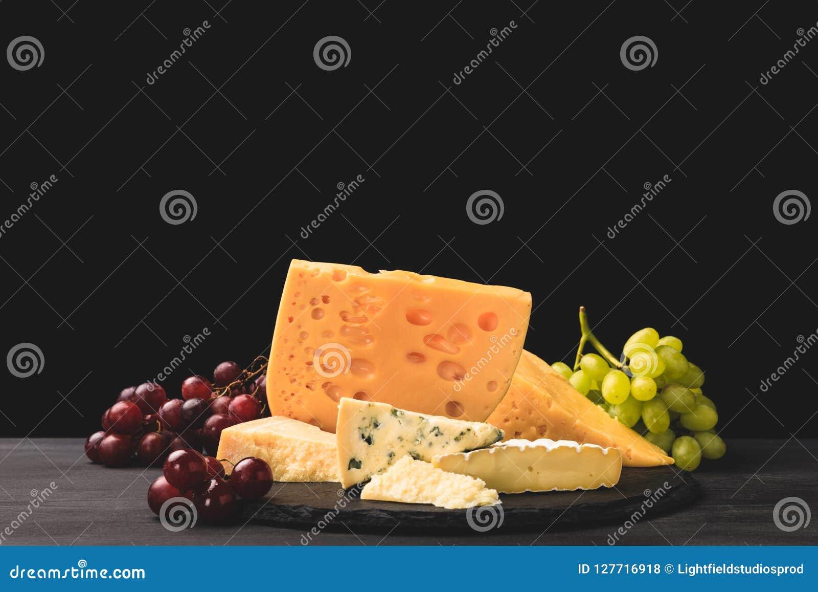Tipi differenti di formaggi a bordo con l uva sul nero