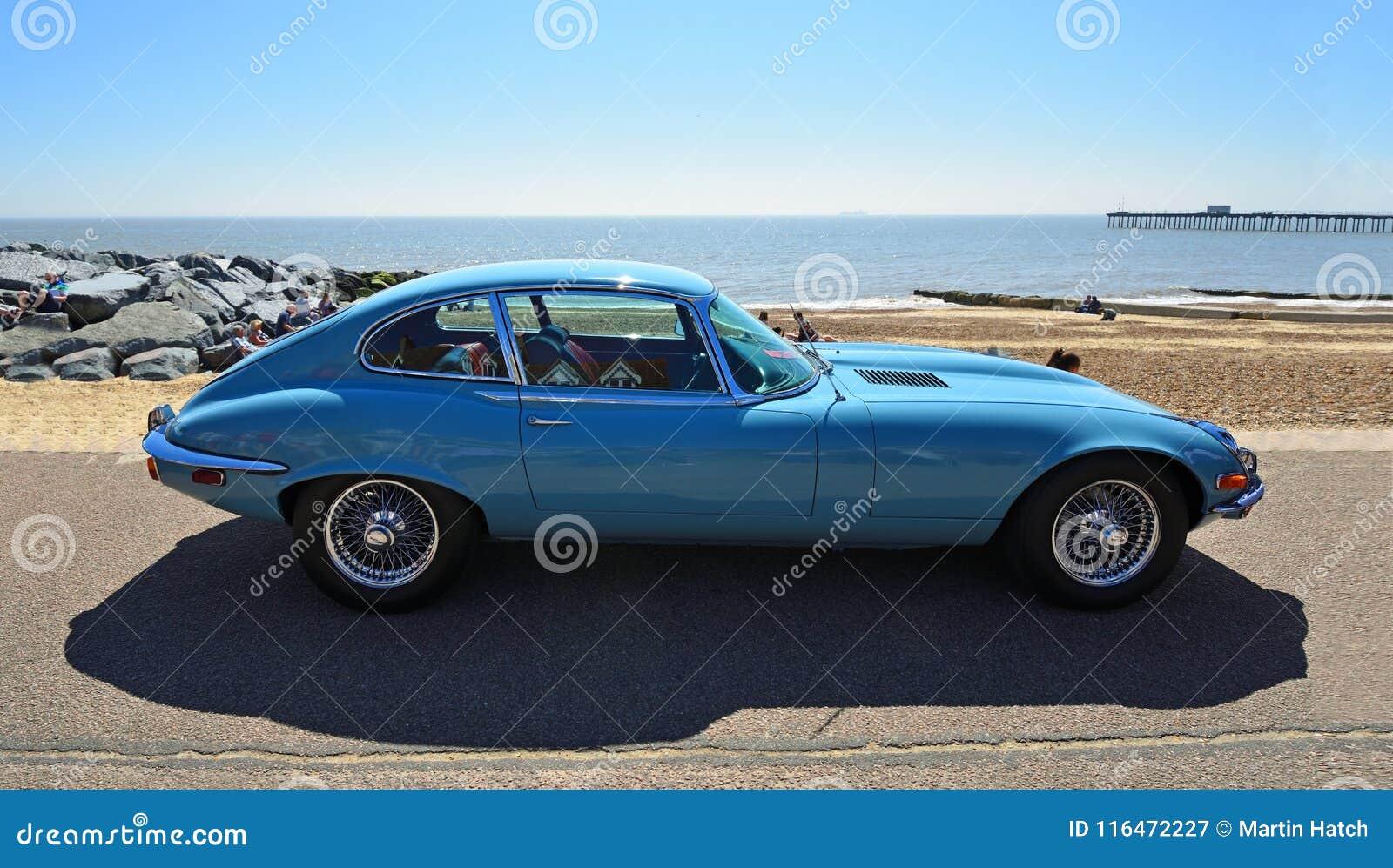 Tipo azul clásico coche de Jaguar E de motor parqueado en la  promenade  de la orilla del mar